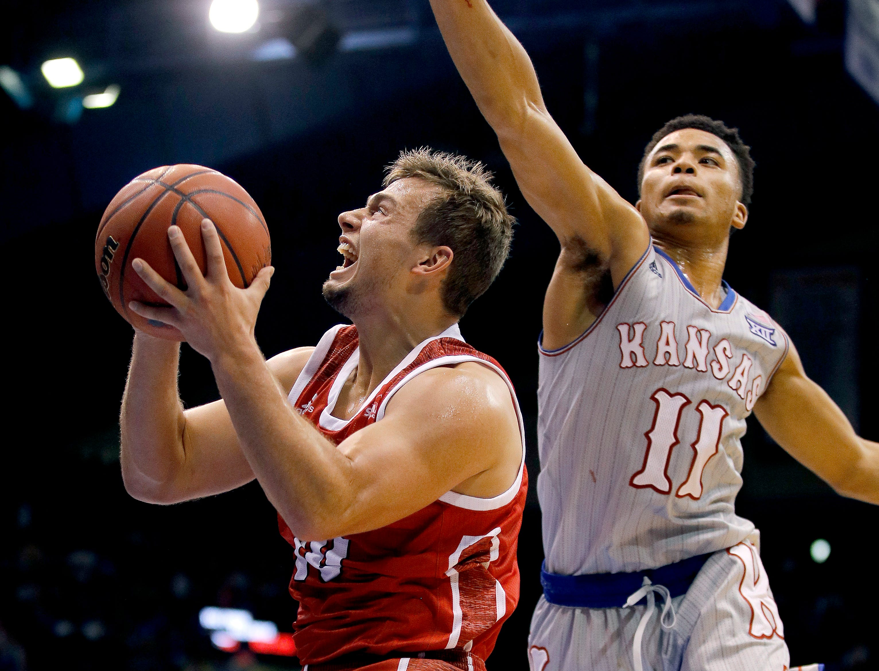 Kansas' Devon Dotson (11) tries to block a shot by South Dakota's Cody Kelley during the second half of an NCAA college basketball game Tuesday, Dec. 18, 2018, in Lawrence, Kan. Kansas won 89-53. (AP Photo/Charlie Riedel)