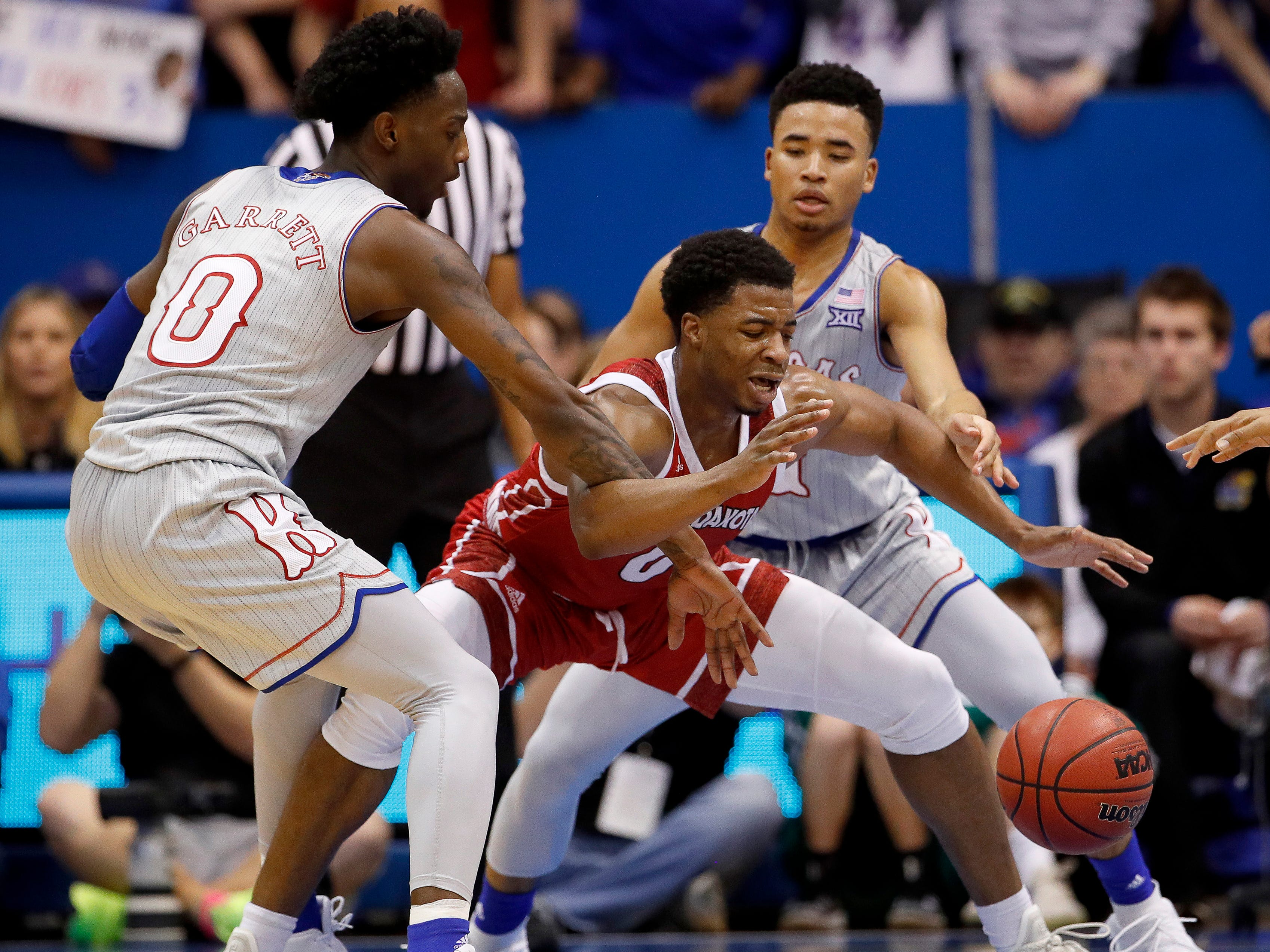 Kansas' Marcus Garrett (0) and Devon Dotson try to strip the ball from South Dakota's Stanley Umude, center, during the first half of an NCAA college basketball game Tuesday, Dec. 18, 2018, in Lawrence, Kan. (AP Photo/Charlie Riedel)