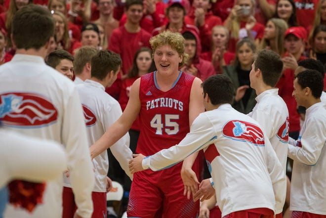 Lincoln's Nate Brecht (45) receives high fives from teammates before the game against Washington, Tuesday, Dec. 18, 2018 at Washington High School in Sioux Falls, S.D.