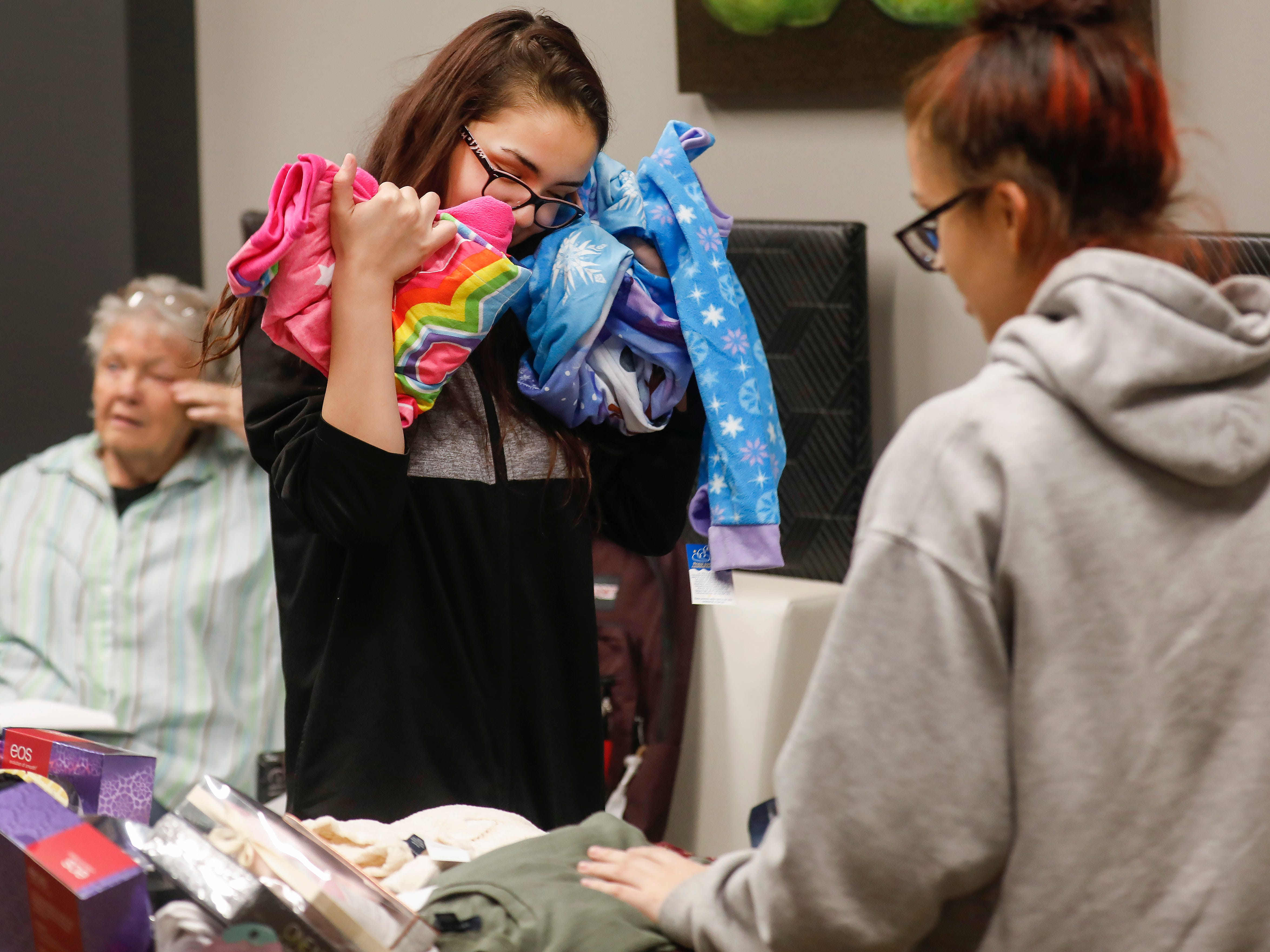 Abigail Sahagun, center, hugs some items of clothing that were a part of the gifts that were given to her and her sisters by employees of J.D. Byrider on Wednesday, Dec. 19, 2018. The Sahaguns' grandmother, Barbara Foster, was killed during a road rage incident on Nov. 20.