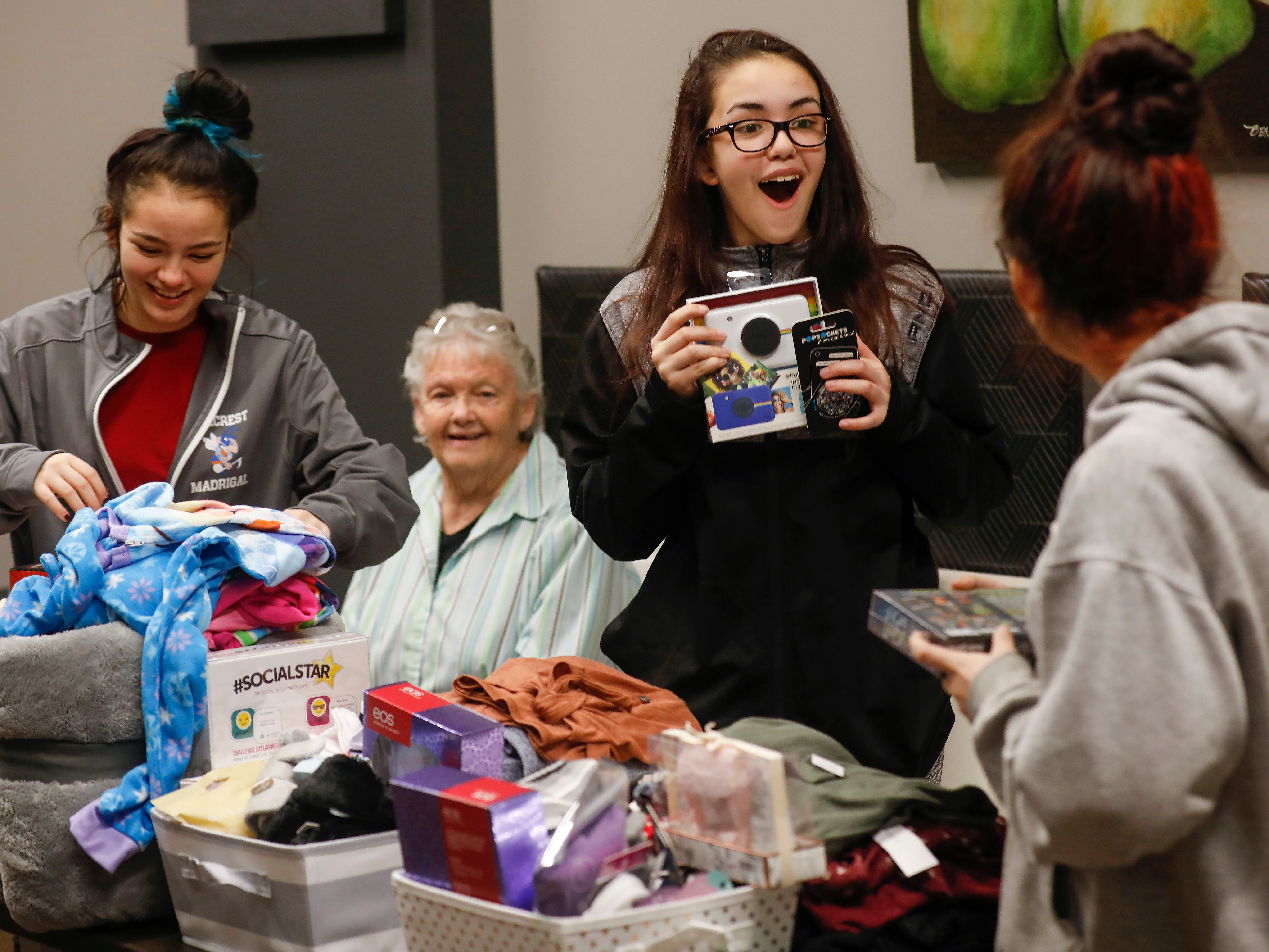 Abigail Sahagun, center, reacts as she looks at gifts that were given to her and her sisters Callie, right, and Emileigh by employees of J.D. Byrider on Wednesday, Dec. 19, 2018. The Sahaguns' grandmother, Barbara Foster, was killed during a road rage incident on Nov. 20.