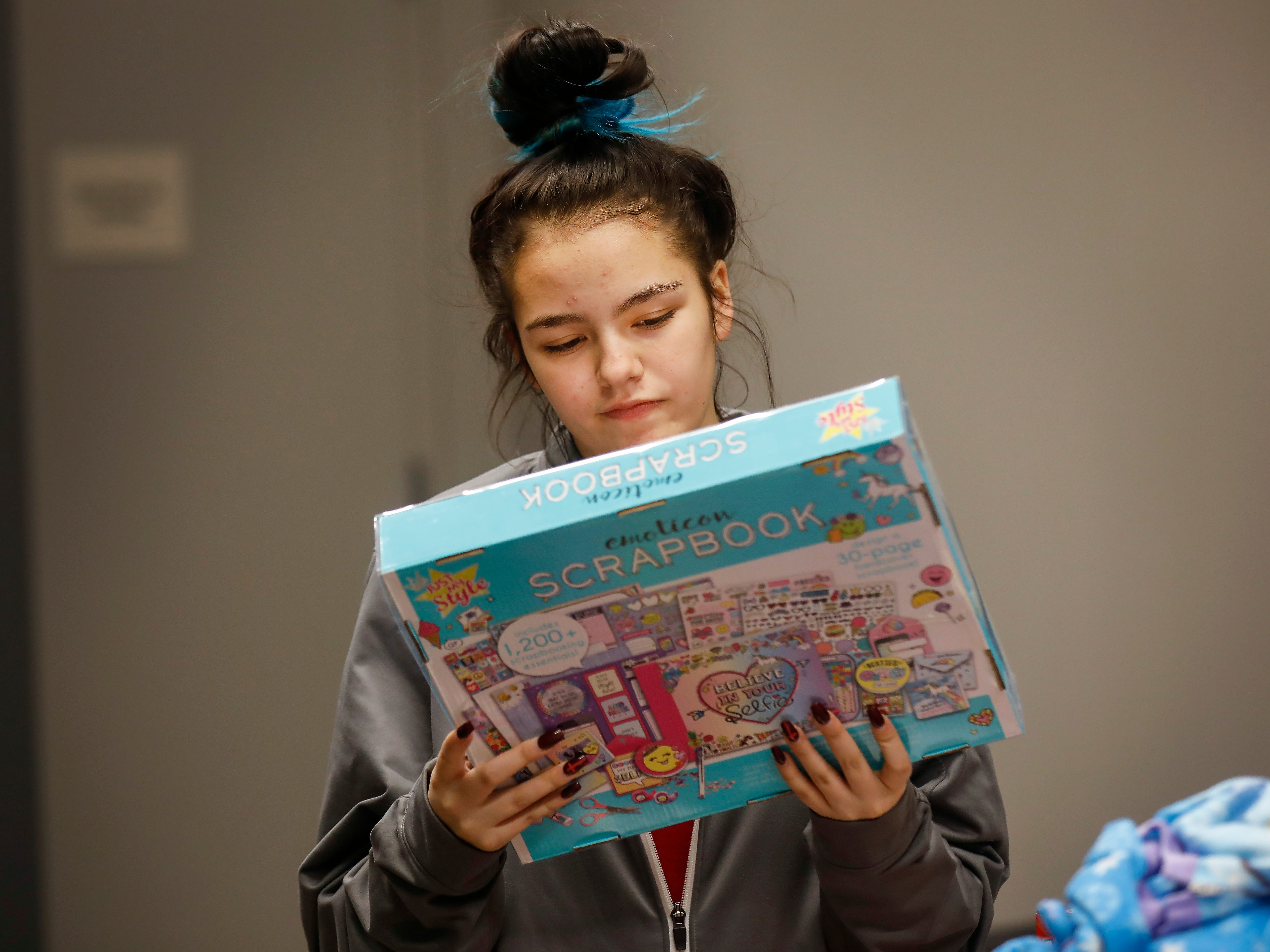 Callie Sahagun looks at one of the gifts that was given to her and her sisters by employees of J.D. Byrider on Wednesday, Dec. 19, 2018. The Sahaguns' grandmother, Barbara Foster, was killed during a road rage incident on Nov. 20.