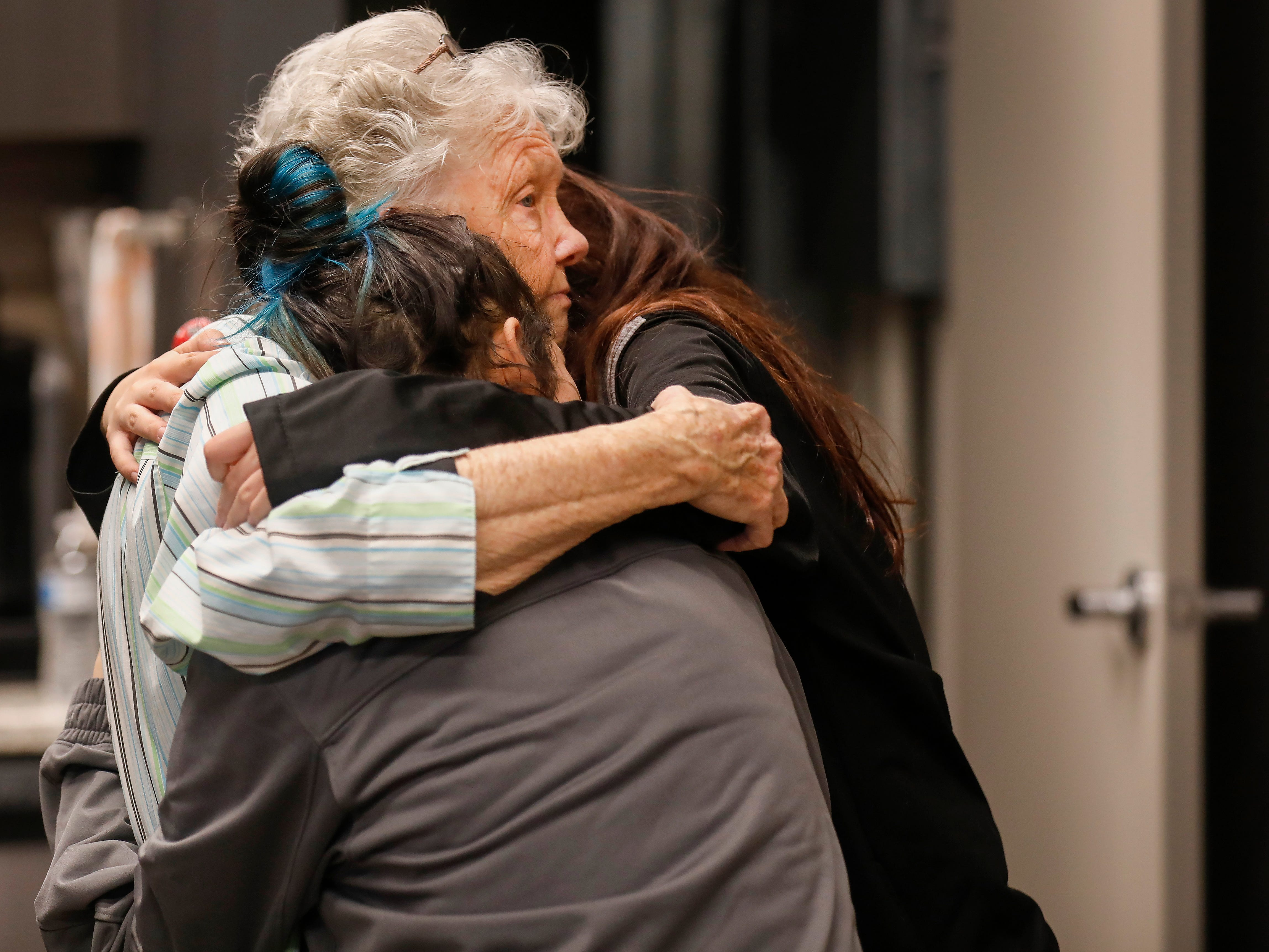Pat Ayers hugs her great granddaughters Abigail Sahagun, right, and Emileigh Sahagun after employees of J.D. Byrider gave them gifts and forgave their car loan on Wednesday, Dec. 19, 2018. Ayers' daughter and the Sahaguns' grandmother, Barbara Foster, was killed during a road rage incident on Nov. 20.