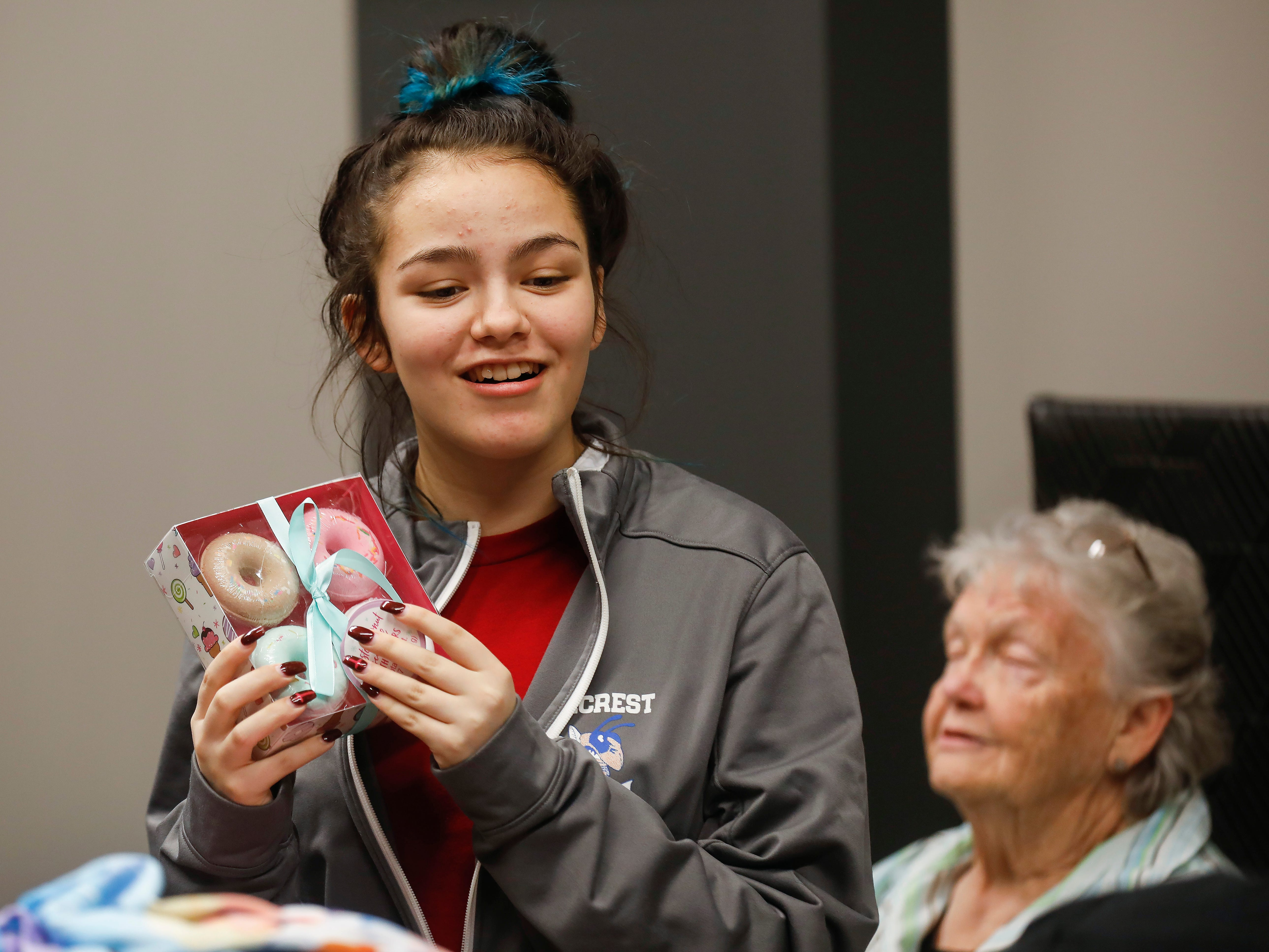 Callie Sahagun, center, shows off one of the gifts that were given to her and her sisters by employees of J.D. Byrider on Wednesday, Dec. 19, 2018. The Sahaguns' grandmother, Barbara Foster, was killed during a road rage incident on Nov. 20.