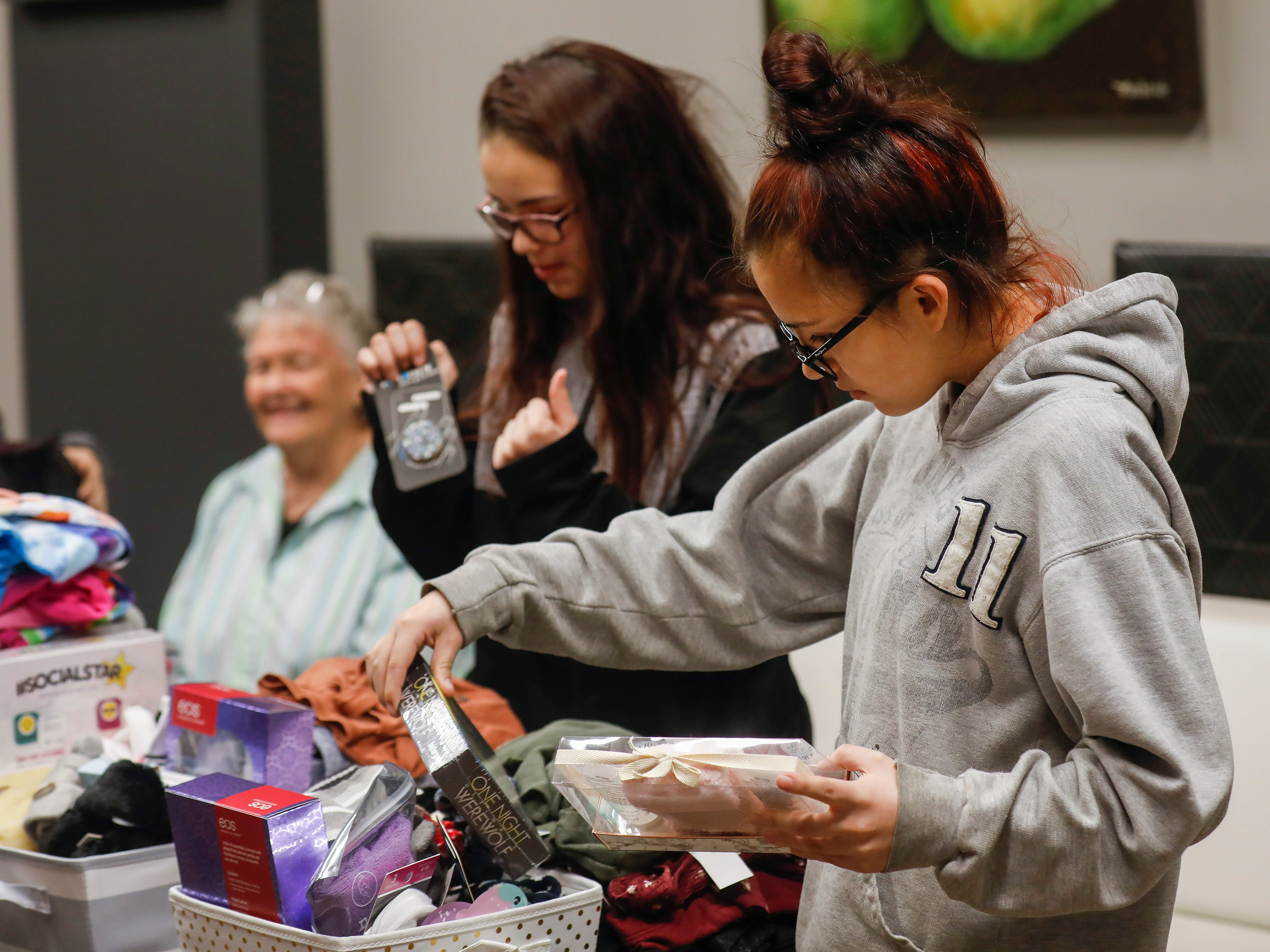 Callie Sahagun, right, looks at gifts that were given to her and her sisters by employees of J.D. Byrider on Wednesday, Dec. 19, 2018. The Sahaguns' grandmother, Barbara Foster, was killed during a road rage incident on Nov. 20.