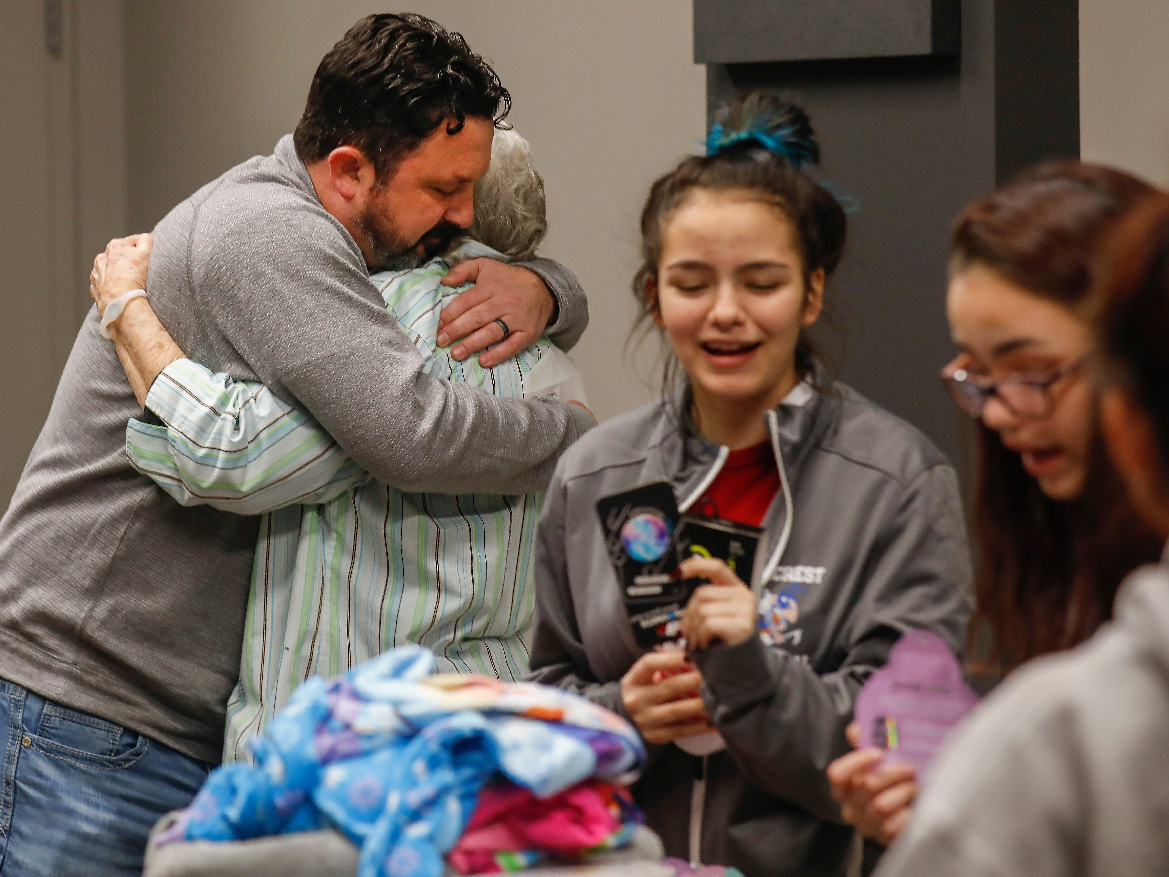 Winston Sleeth, owner of J.D. Byrider in Springfield, hugs Pat Ayers after he told her that her daughter's car loan had been forgiven on Wednesday, Dec. 19, 2018. Ayers' daughter, Barbara Foster, was killed during a road rage incident on Nov. 20. Pictured to the right, Ayers' great-granddaughters react as they look through gifts given to them by employees of J.D. Byrider.