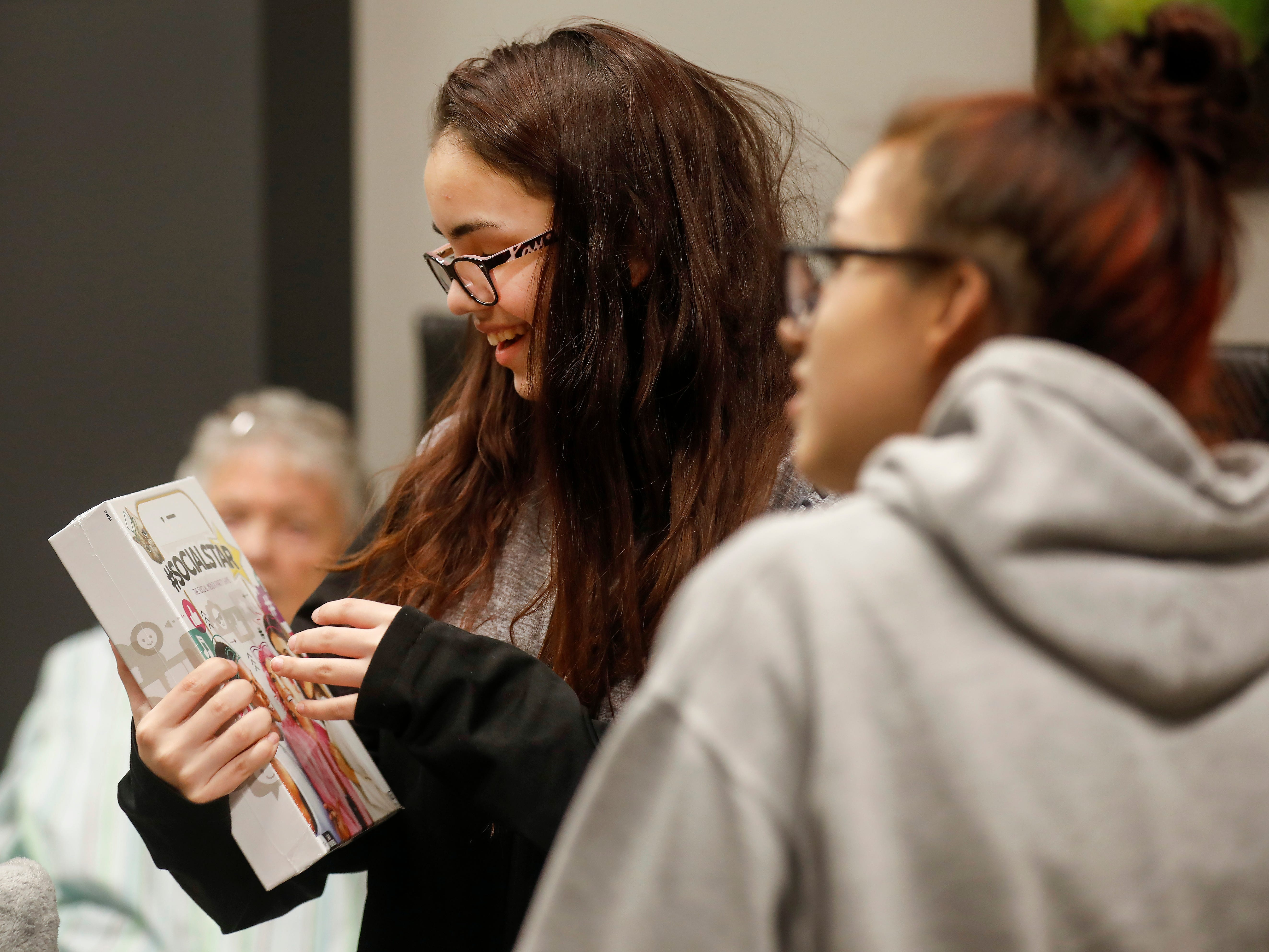 Abigail Sahagun, center, reacts as she looks at gifts that were given to her and her sisters by employees of J.D. Byrider on Wednesday, Dec. 19, 2018. The Sahaguns' grandmother, Barbara Foster, was killed during a road rage incident on Nov. 20.