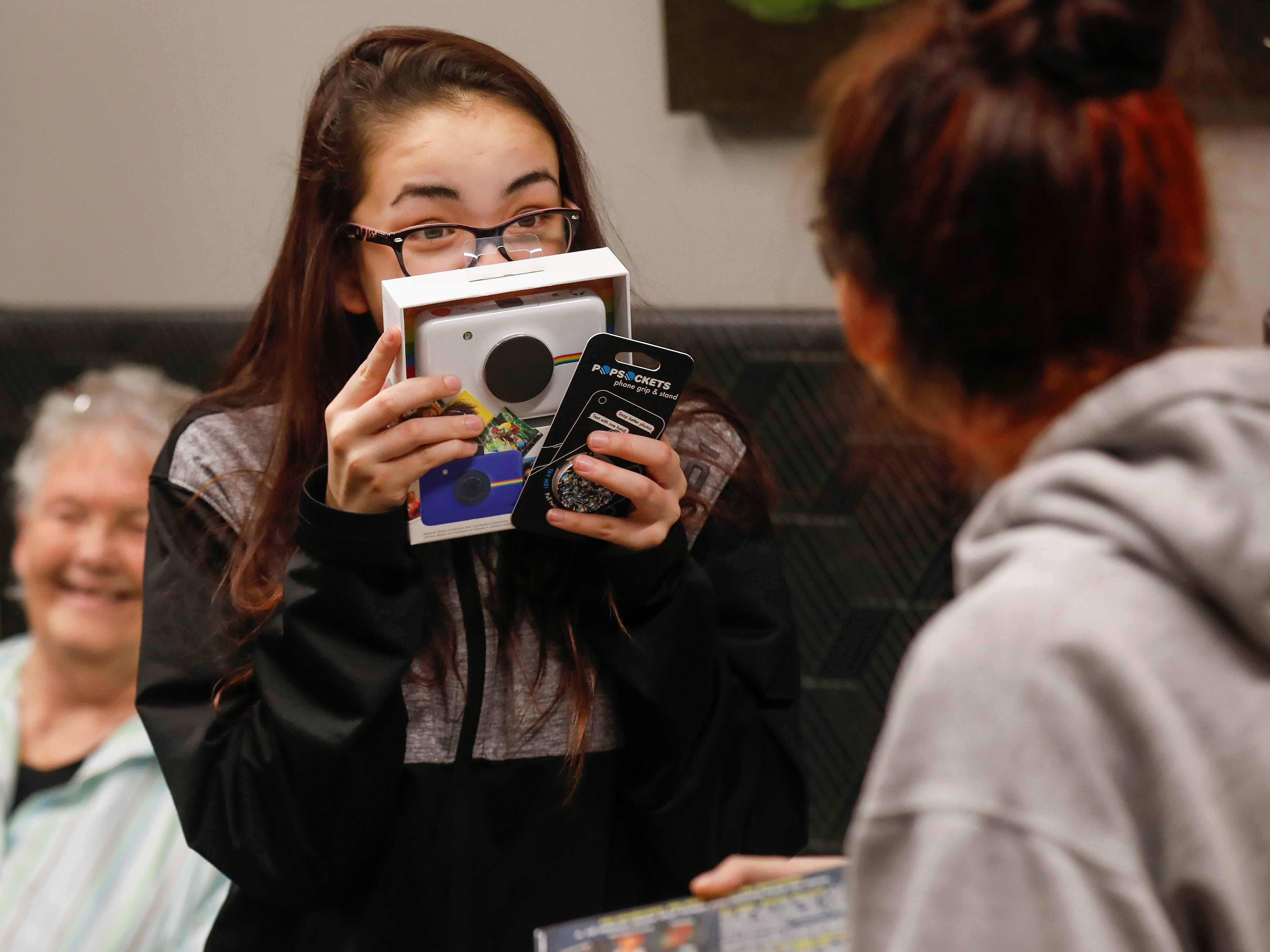 Abigail Sahagun, center, reacts excitedly as she looks at gifts that were given to her and her sisters by employees of J.D. Byrider on Wednesday, Dec. 19, 2018. The Sahaguns' grandmother, Barbara Foster, was killed during a road rage incident on Nov. 20.