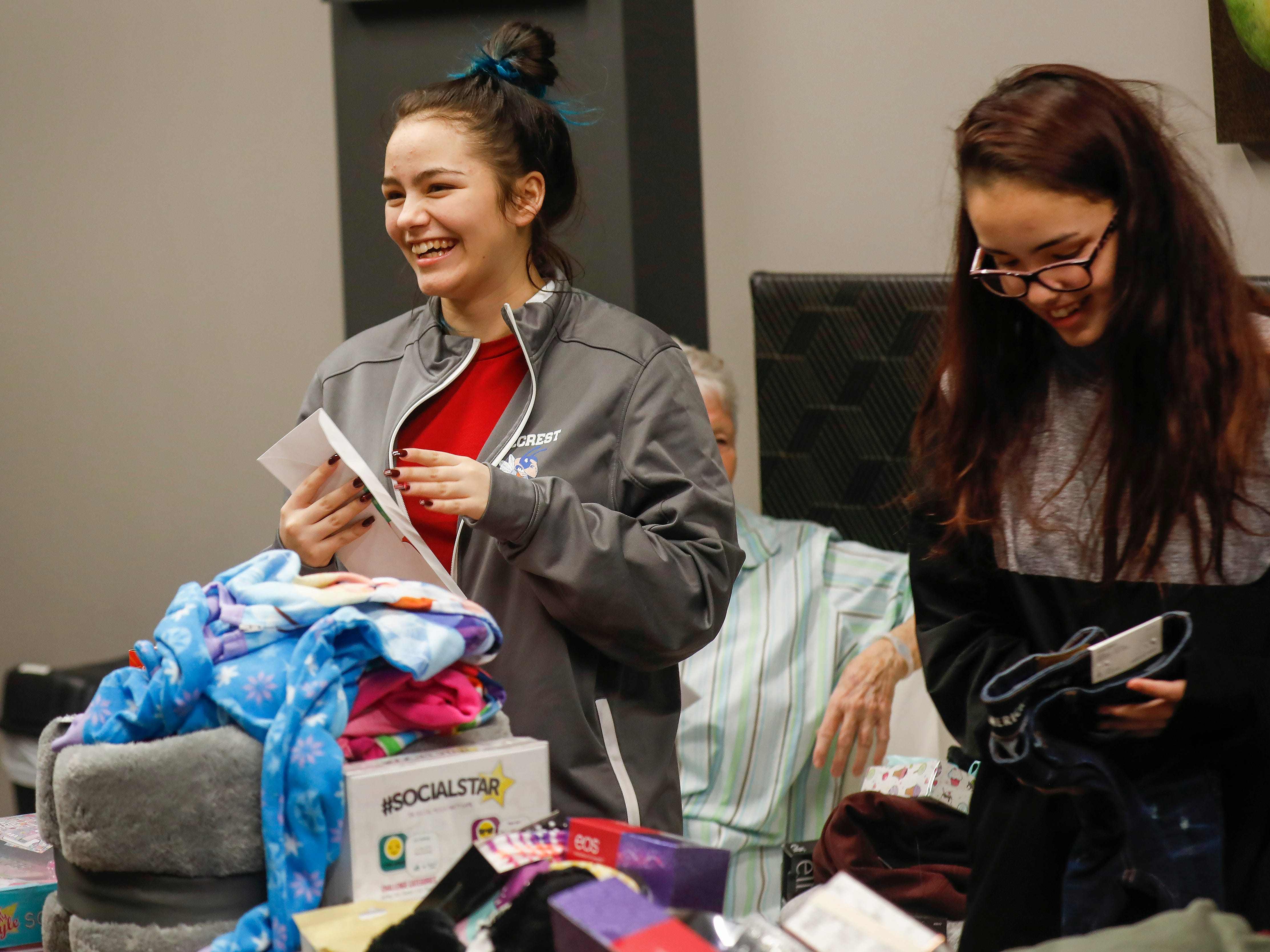 Callie Sahagun, left, and Abigail Sahagun laugh as they look through gifts that were given to them by employees of J.D. Byrider on Wednesday, Dec. 19, 2018. The Sahaguns' grandmother, Barbara Foster, was killed during a road rage incident on Nov. 20.
