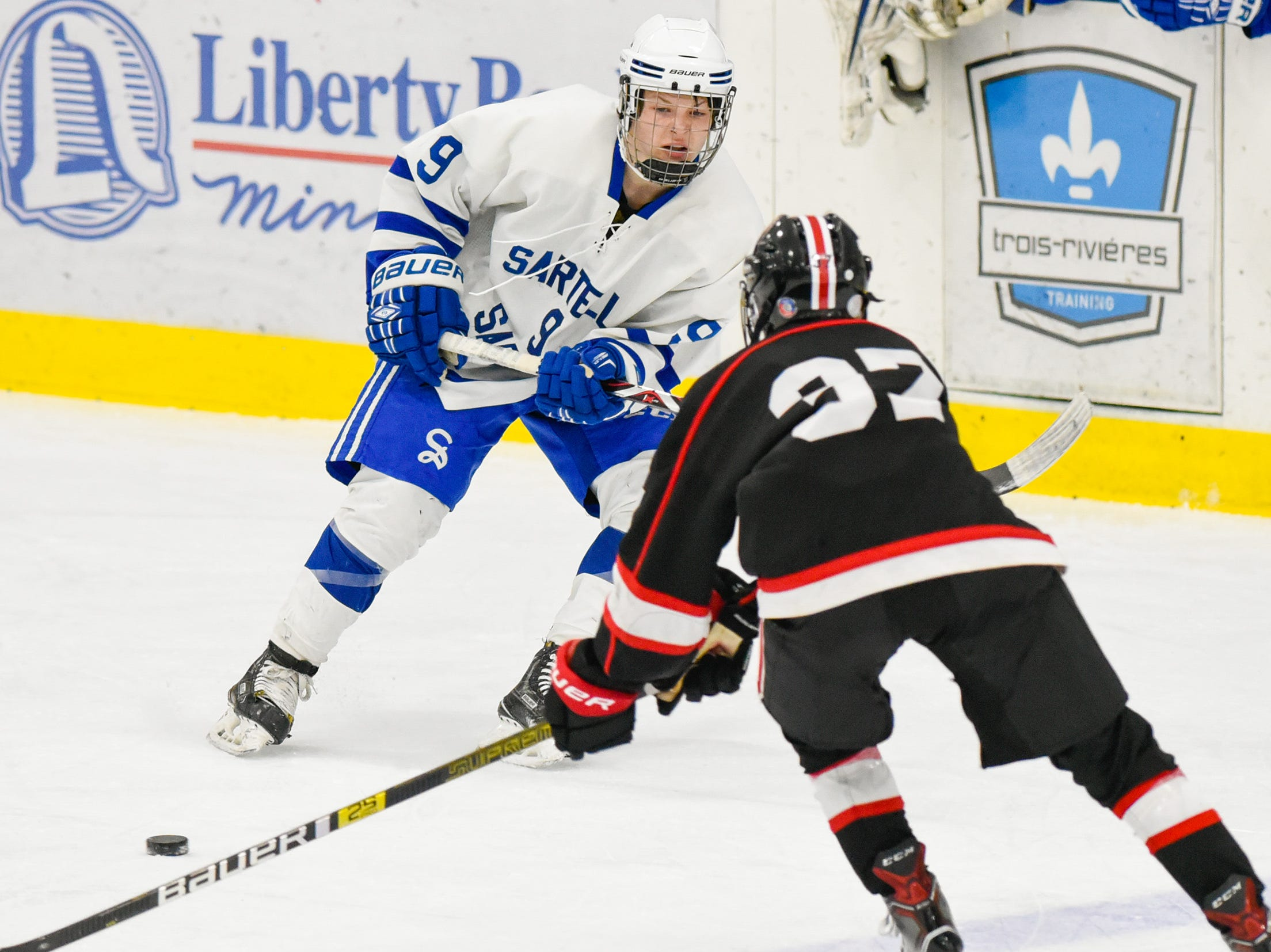 Sartell's Hayden Walters passes the puck past St. Cloud's Luke Johnson during the first period Tuesday, Dec. 18, at the Bernick's Arena in Sartell.