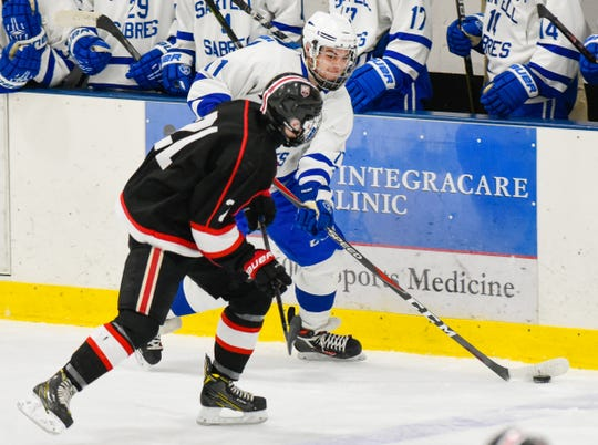 Sartell's Nathan Stoebe passes around St. Cloud's Nick Richert during the first period Tuesday, Dec. 18, at the Bernick's Arena in Sartell.