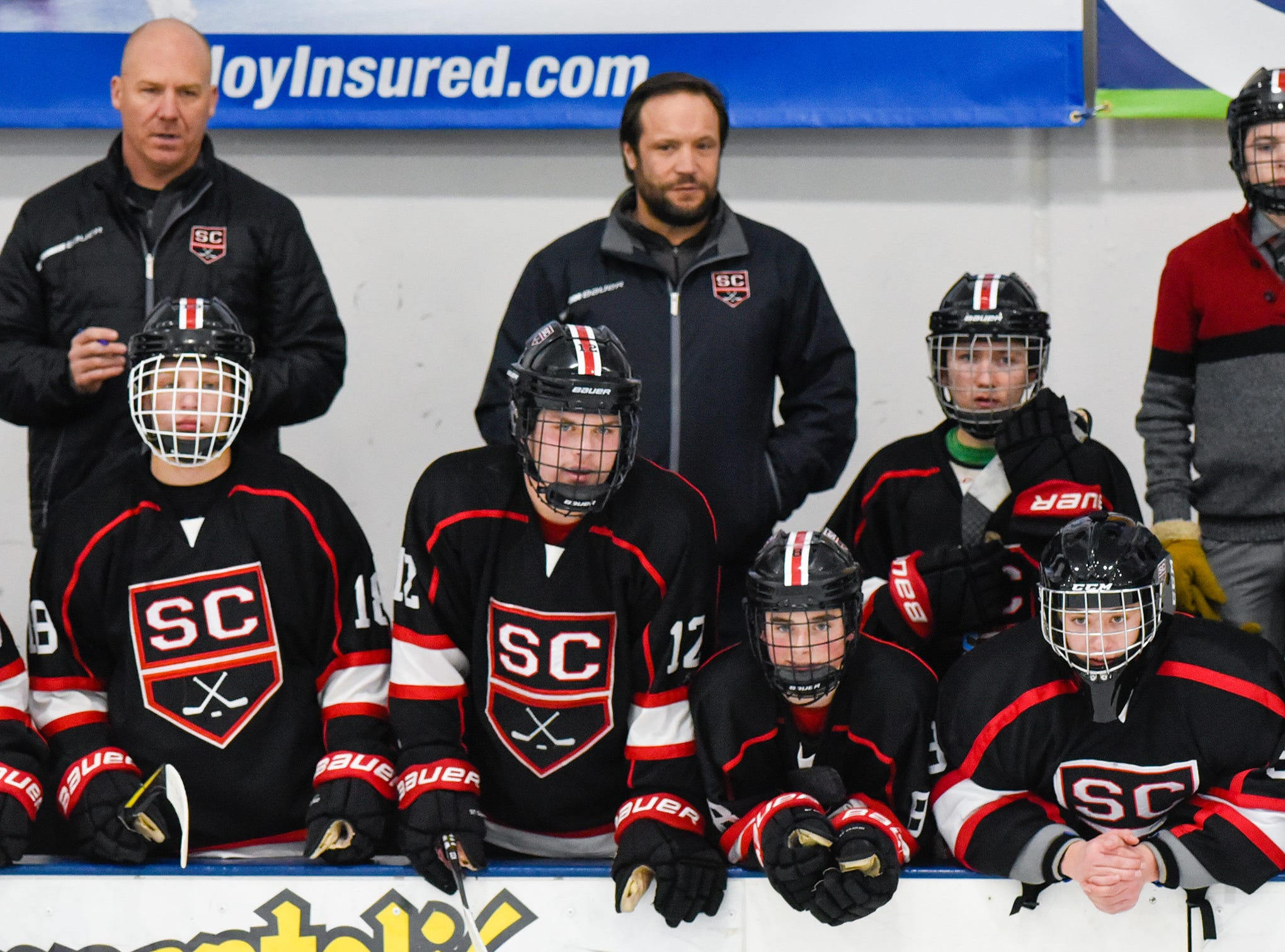 St. Cloud players and coaches watch the action from the bench during the first period Tuesday, Dec. 18, at the Bernick's Arena in Sartell.