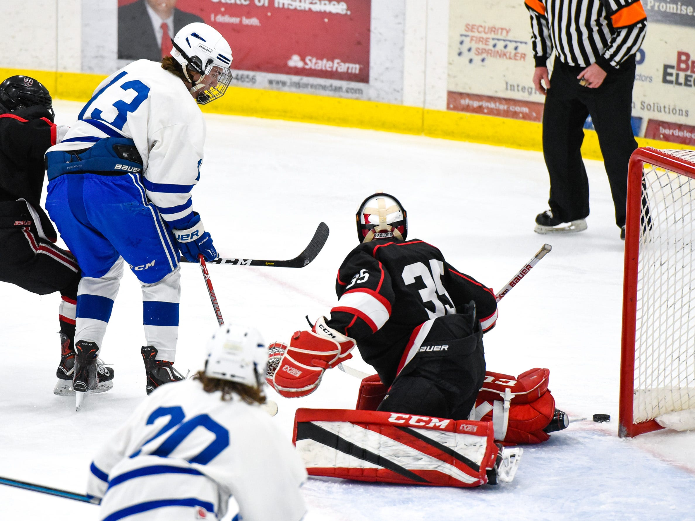 Sartell's Ryan Zulkosky, 13,  has his shot pushed wide by St. Cloud goalie Soren Falloon during the first period Tuesday, Dec. 18, at the Bernick's Arena in Sartell.