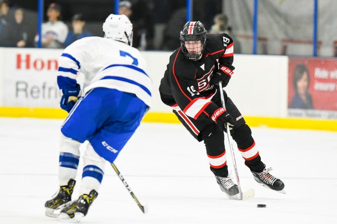 St. Cloud's Sam Oster skates with the puck around Sartell's Cameron Cromwell during the second period Tuesday, Dec. 18, at the Bernick's Arena in Sartell.