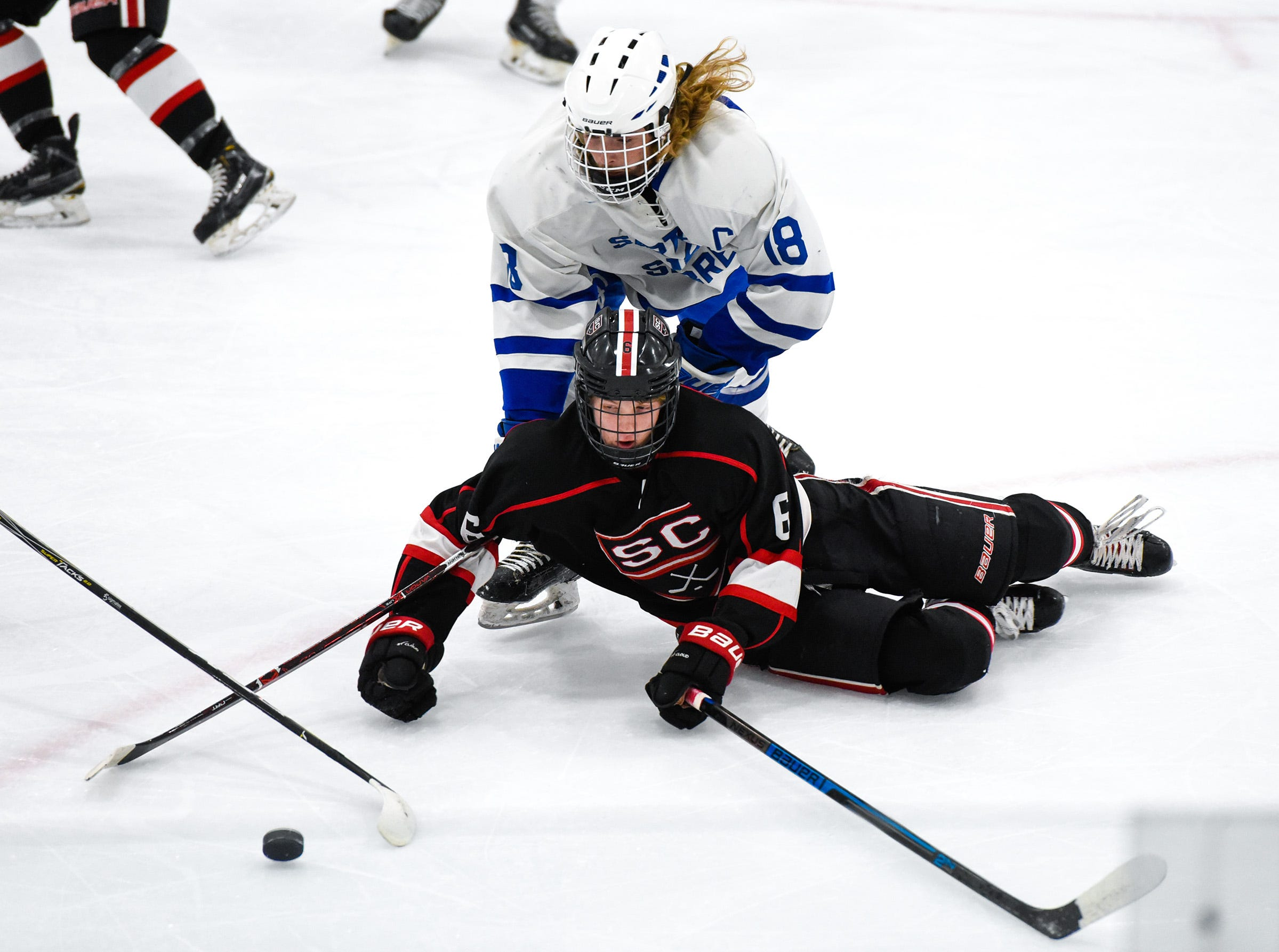 St. Cloud's Eric Warner and Sartell's Jack Hennemann go after the puck during the first period Tuesday, Dec. 18, at the Bernick's Arena in Sartell.