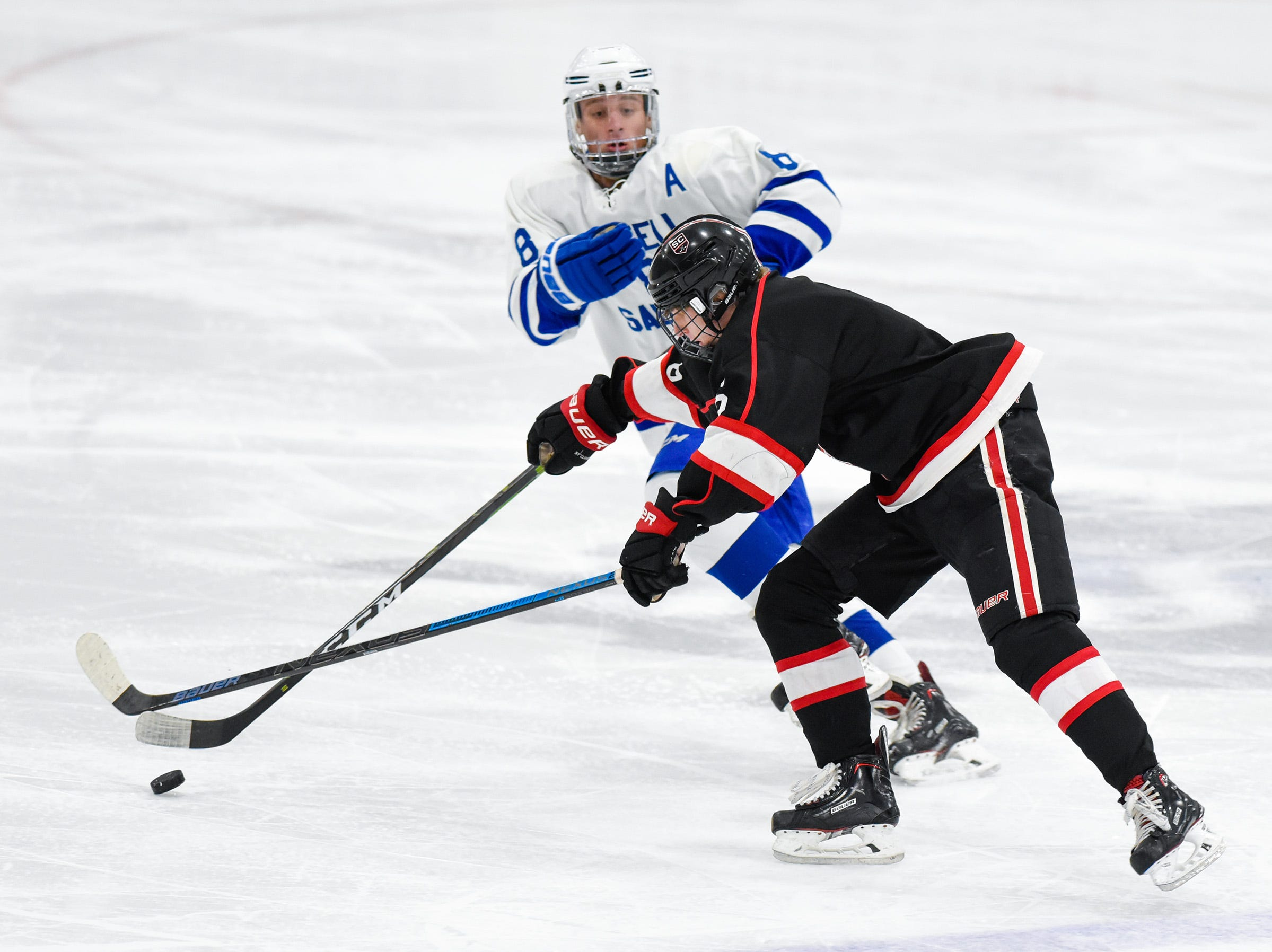 St. Cloud's Eric Warner takes the puck past Sartell's Connor Kalthoff during the first period Tuesday, Dec. 18, at the Bernick's Arena in Sartell.