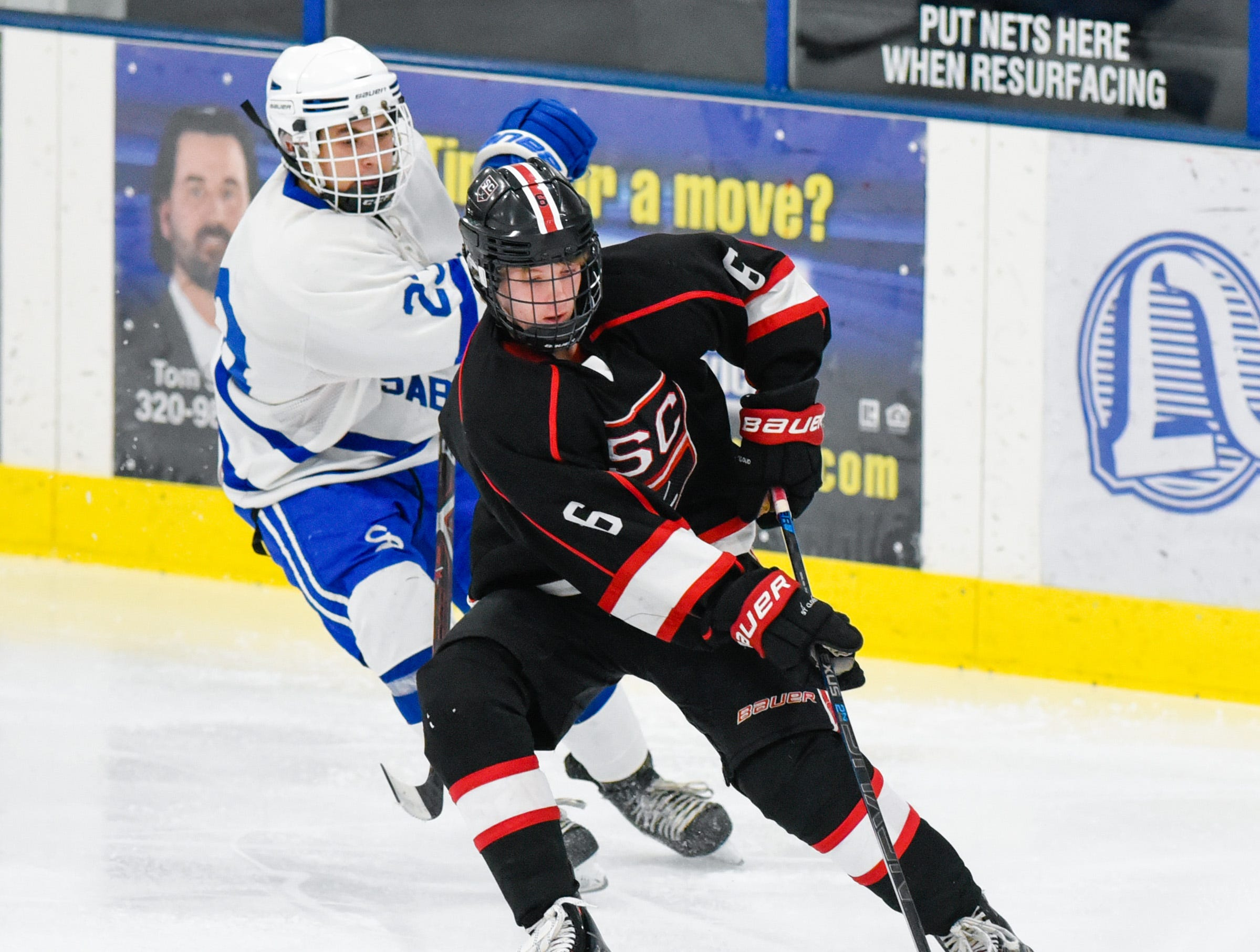 St. Cloud's Eric Warner keeps the puck away from Sartell's Nicholas Buiceag-Arama during the first period Tuesday, Dec. 18, at the Bernick's Arena in Sartell.