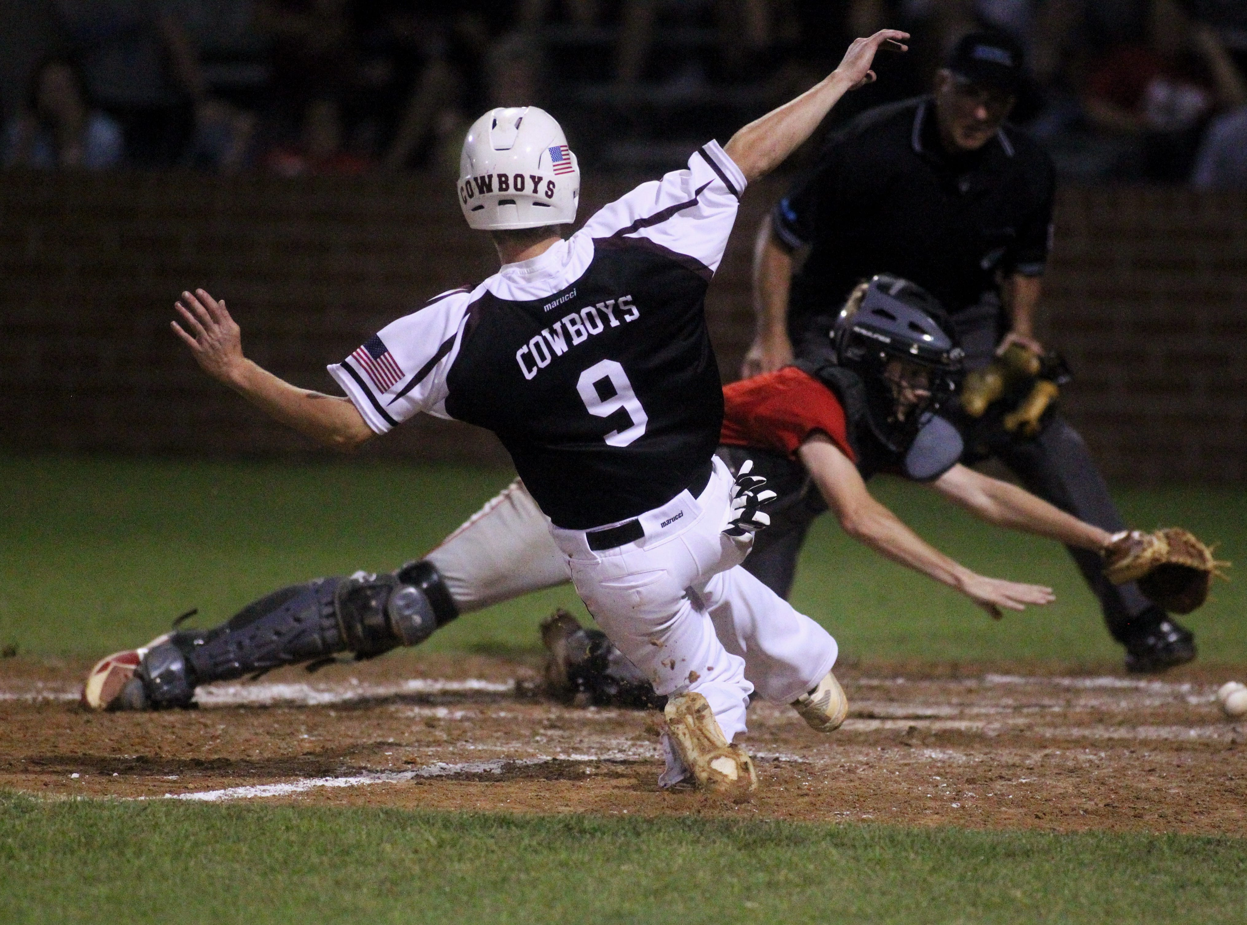 Madison County senior Dylan Bass slides into home plate as a relay throw gets away from Lafayette's catcher, leading to a walk-off victory in extra innings in a regional final.