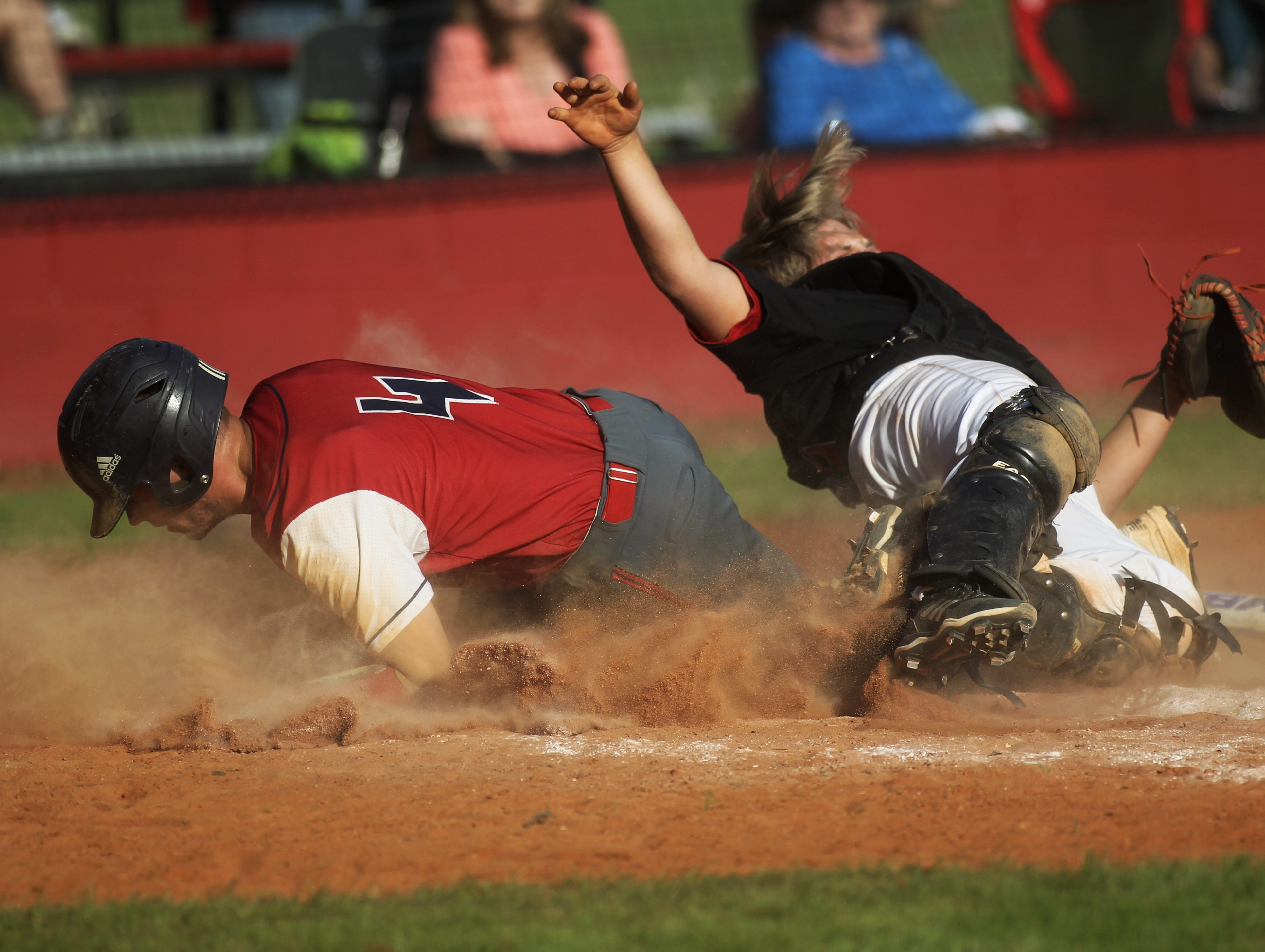 Wakulla Christian's Aaron Collins wipes out Robert F. Munroe catcher Jackson Boone on a hard slide on a play at the plate during a spring baseball game at Munroe.