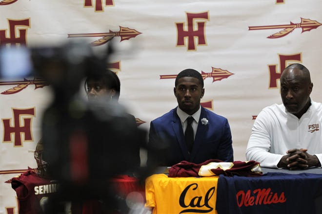 Florida High senior defensive back Raymond Woodie III sits next to his father Raymond Woodie Jr., who is Florida State's linebackers coach. Woodie III signed Wednesday to play at FSU.
