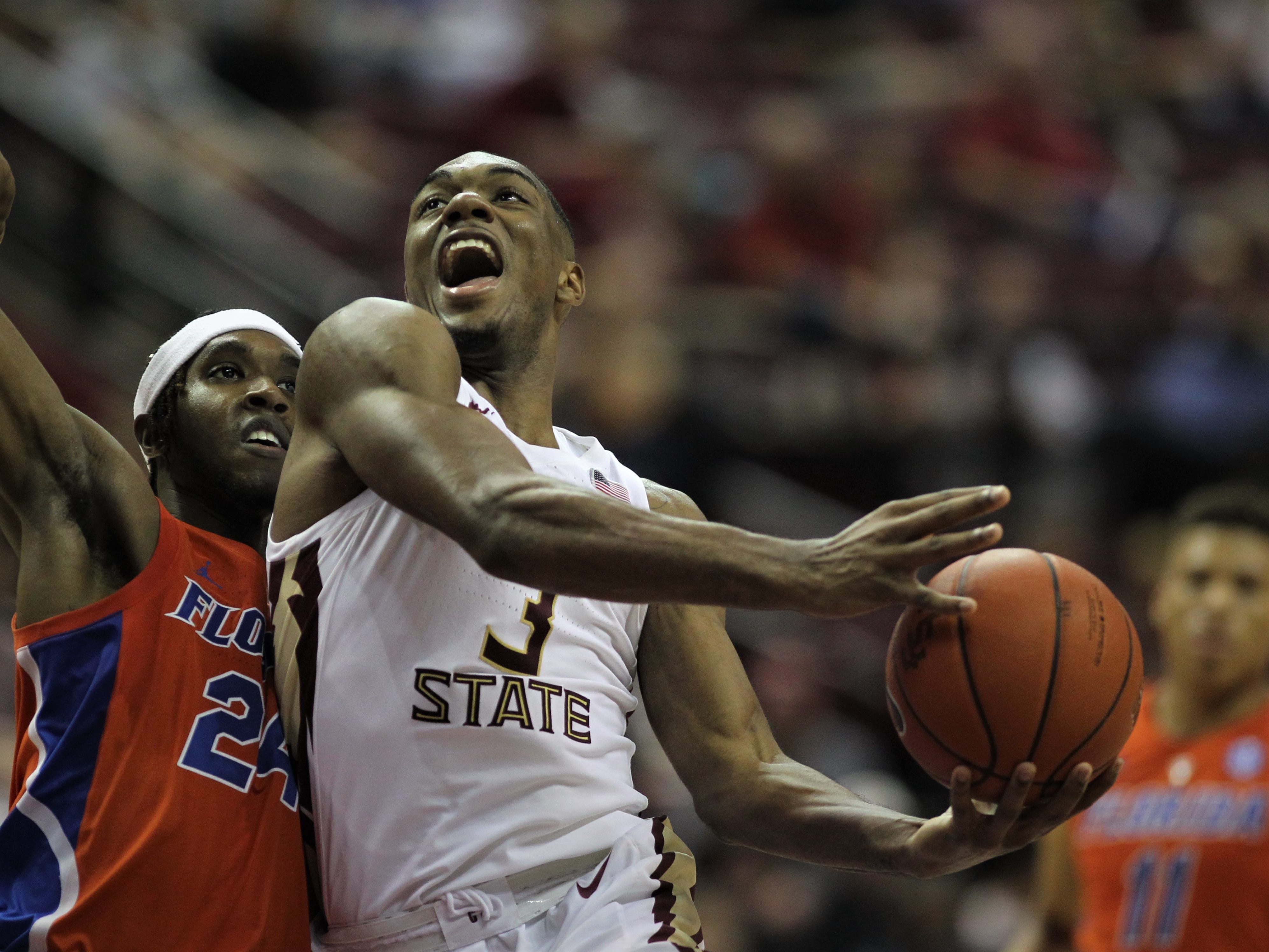 Florida State's Trent Forrest glides through the air for a left-handed layup as a Florida player defends during the two teams' game at the Tucker Civic Center on Nov. 11, 2018.