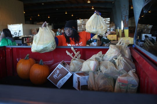 Angie Riviere, a first time volunteer, loads up a truck as Farm Share provides roughly 1,000 meals for families in Quincy, during last year's distribution. This year's pre-Thanksgiving distribution will be Friday.