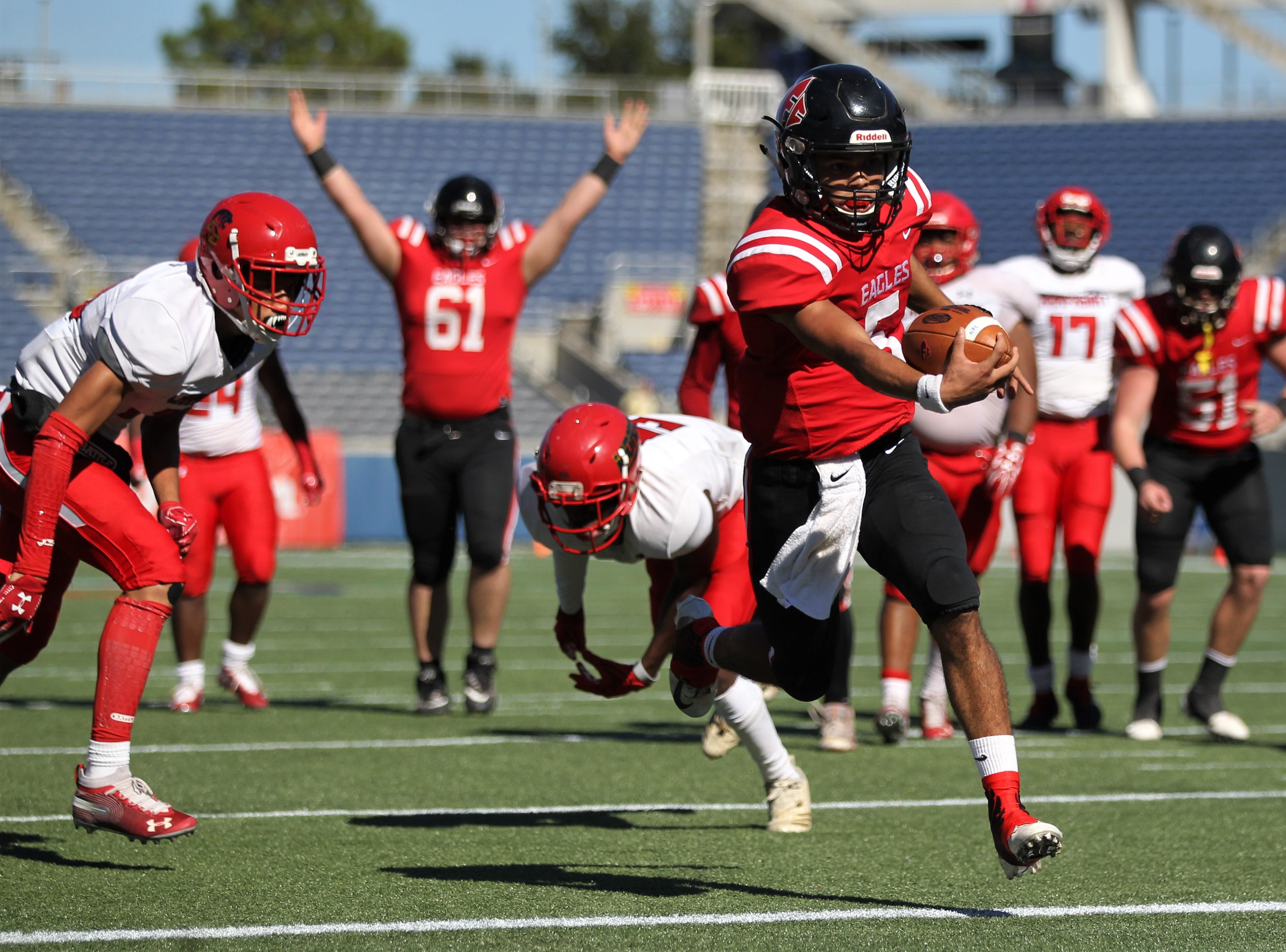 North Florida Christian senior quarterback J.D. Jerry escapes Champagnat Catholic tacklers to score a a crucial touchdown that helped the Eagles win 28-20 and capture a Class 2A state championship on Friday, Dec. 7, 2018.