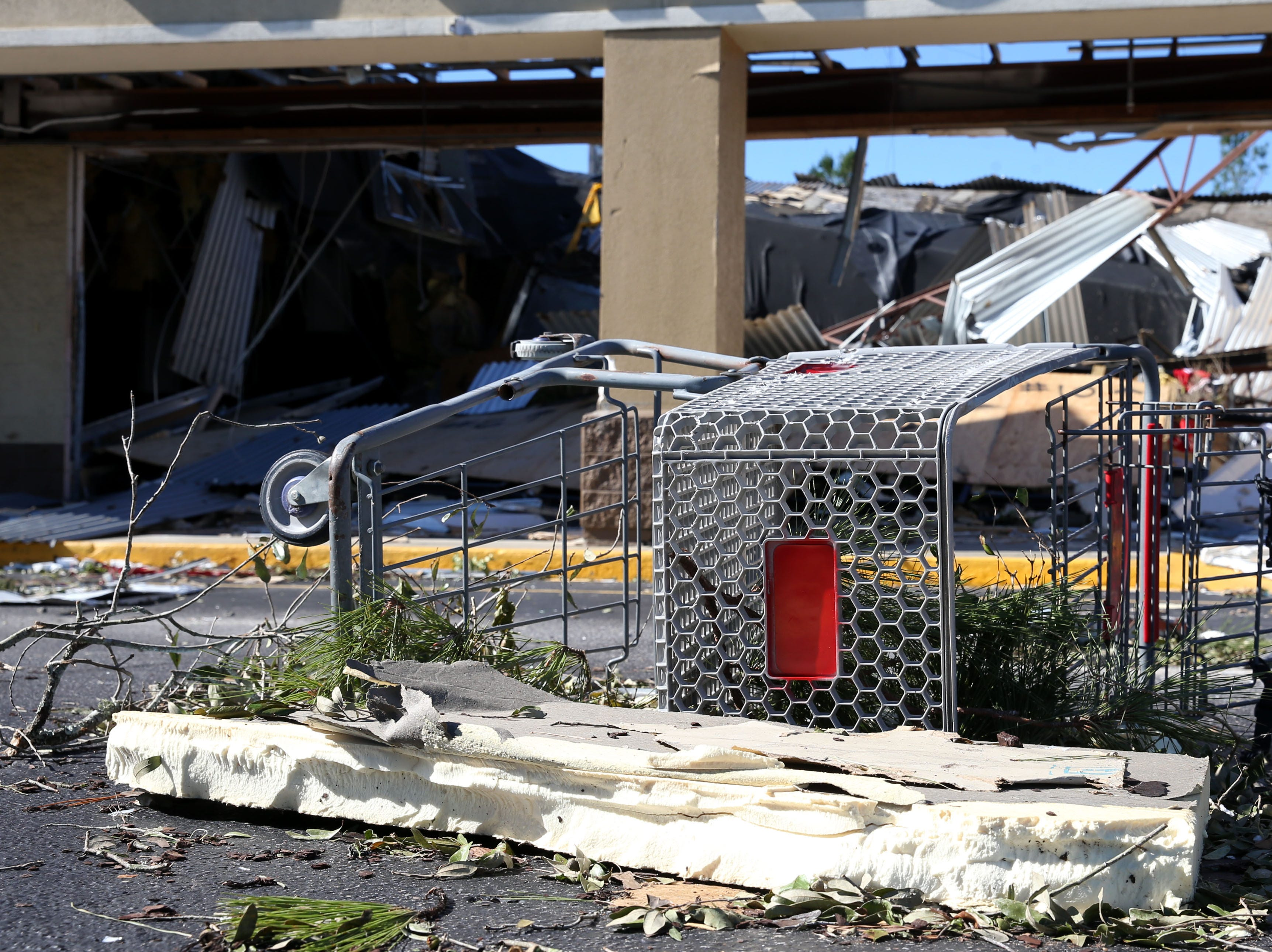 A displaced shopping cart rests outside of the Oak Station shopping plaza in Marianna, Fla. after Hurricane Michael ripped through the panhandle on Wednesday, Oct. 10, 2018. The plaza roof was torn off due to the strong winds and the windows were shattered by flying debris. A team of security  guards were placed outside the plaza to prevent looters from stealing merchandise, Friday Oct. 12, 2018.