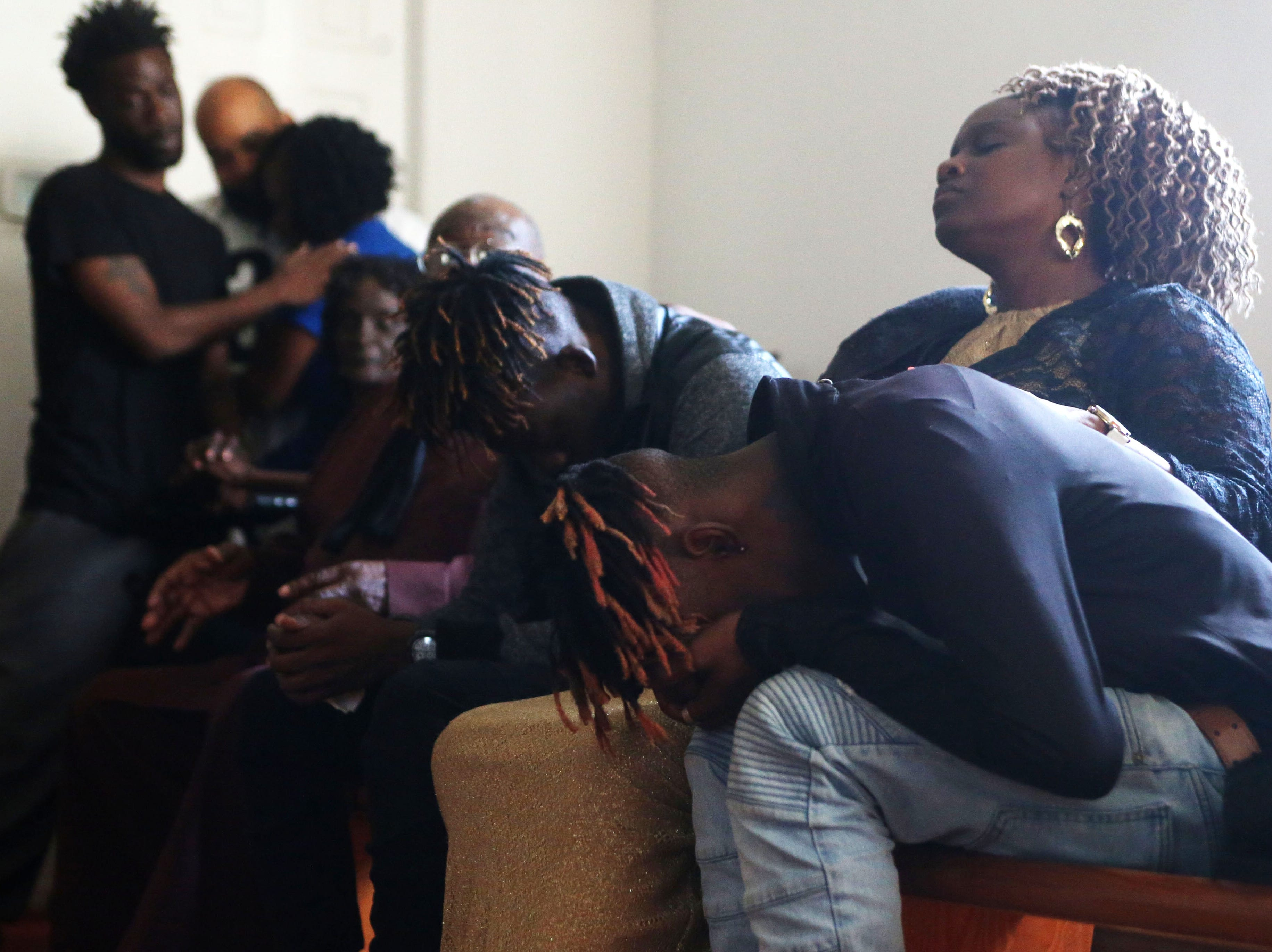 Jeanella Hall, 38, aunt, middle consoles Tyrone Grant, 23, left, and Tyran Grant, 21, right, sons of Demashell Bass, a woman who died because she could not receive medical attention and died during Hurricane Michael, at the Dream, Vision, and Destiny (DVD) Ministry in Gretna, Fla., on Sunday Oct. 14, 2018. The hurricane hit Florida Wednesday, Oct. 10, 2018 and left many rural towns devastated and without power for days.