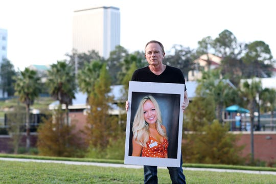 Jeff Binkley, father of Maura Binkley, a Florida State University student killed in the shooting at Hot Yoga Tallahassee, poses at Cascades Park with a photo his daughter before speaking at a vigil in honor of the victims, Sunday, Nov. 11, 2018.