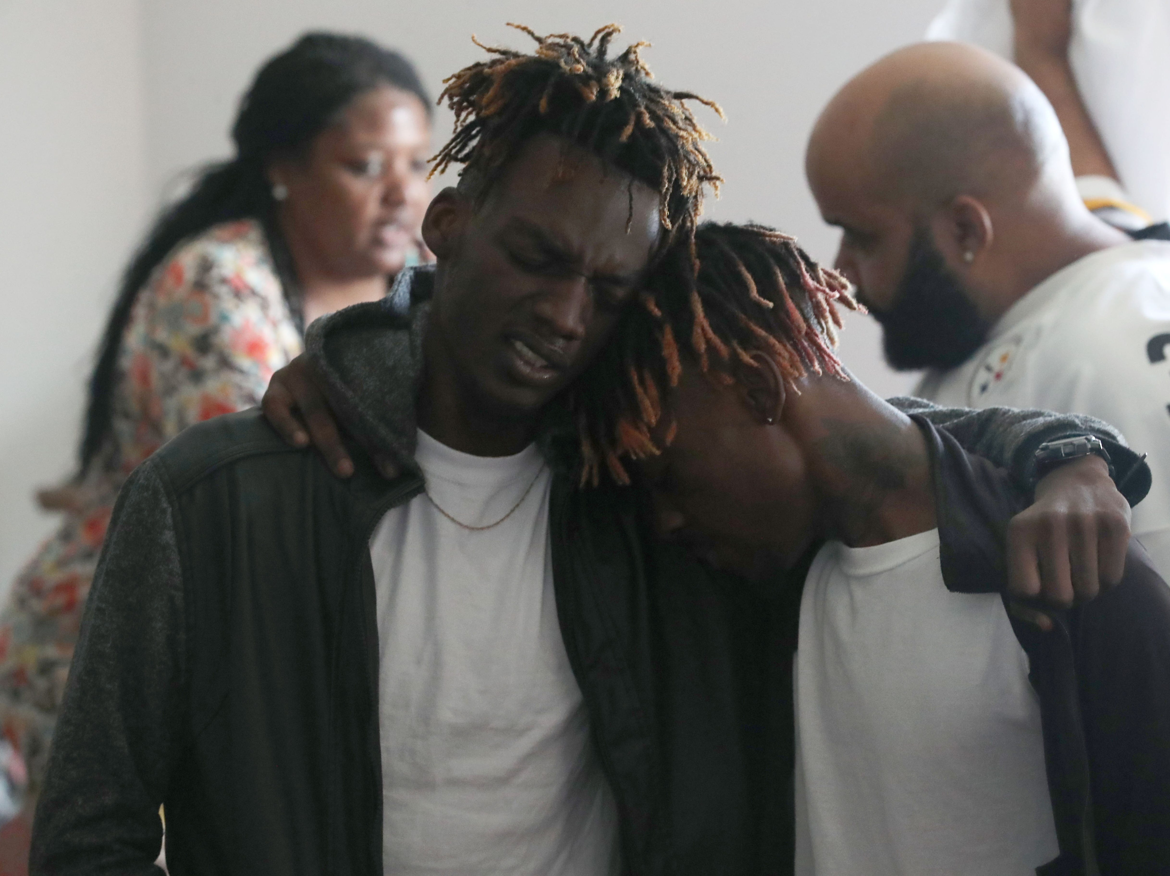 Tyrone Grant, 23, left, and his brother Tyran Grant, 21, both sons of  Demashell Bass, a woman who could not receive medical attention and died during Hurricane Michael, lean on one another while Tyrone sings a hymnal during church service at the Dream, Vision, and Destiny (DVD) Ministry in Gretna, Fla., on Sunday Oct. 14, 2018. Emotions flowed throughout the sanctuary as the service progressed and church members mourn the loss of Bass.