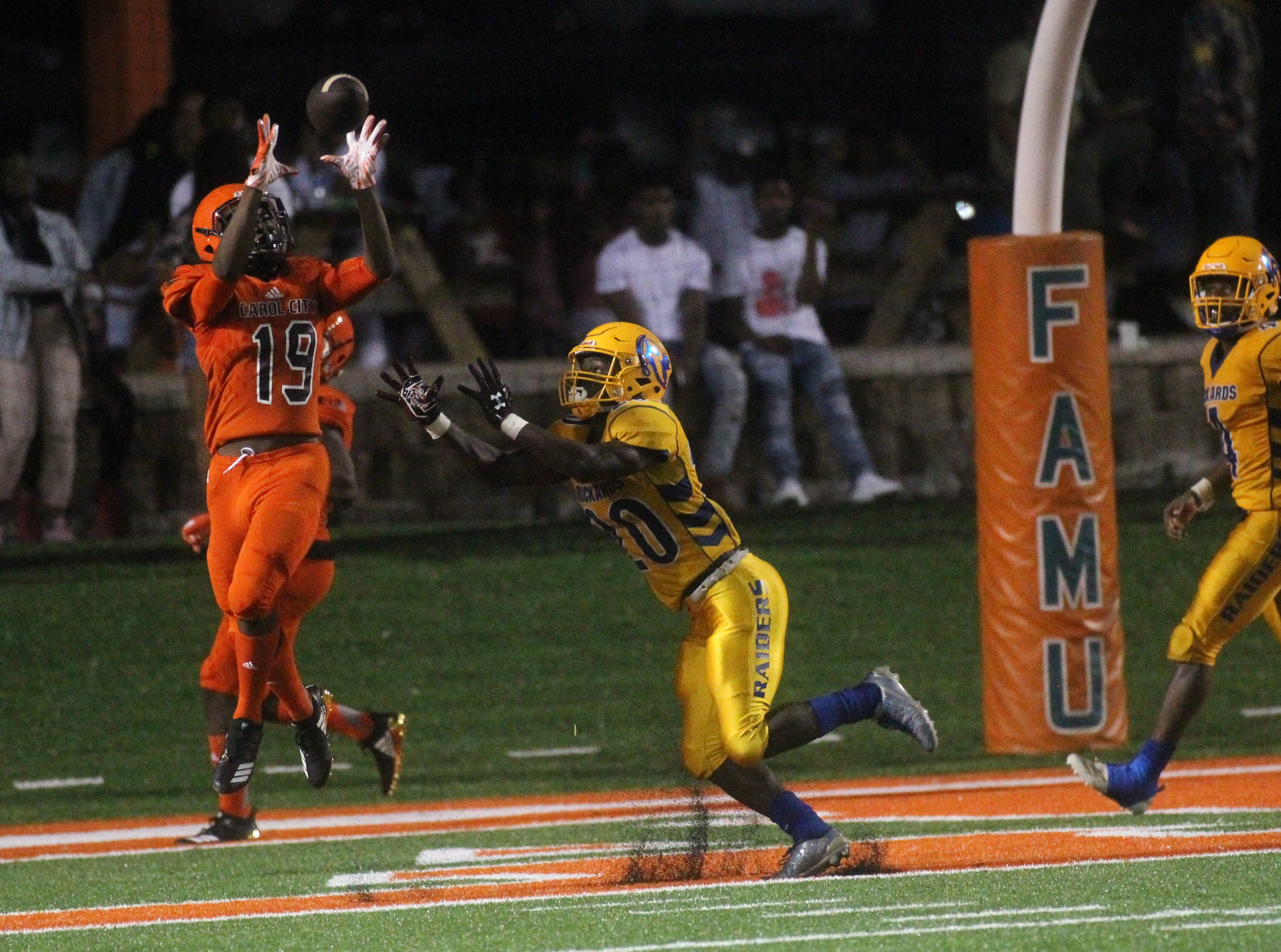 A Miami Carol City receiver hauls in a touchdown catch over a Rickards High defender during a preseason game at Florida A&M's Bragg Memorial Stadium. The field had just gotten brand new artificial turf.