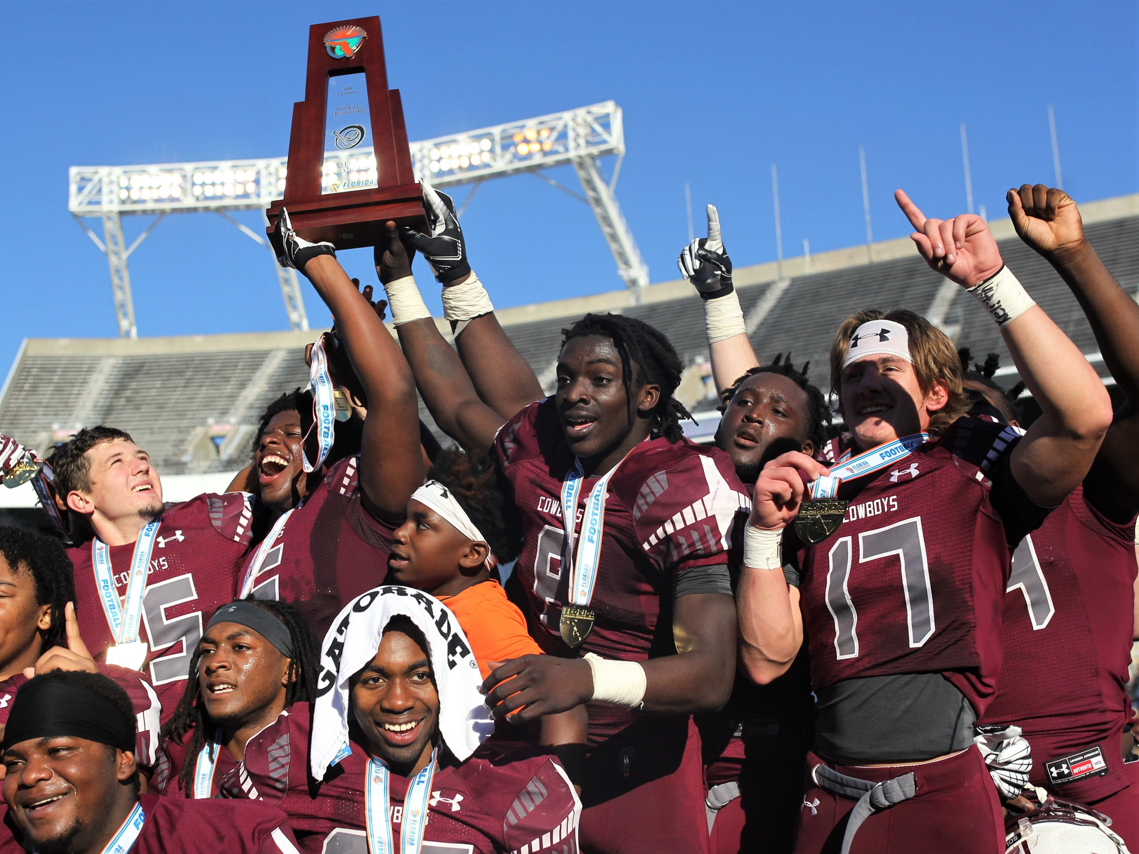 Madison County's Travis Jay (18) and Patrick Hampton (6) hold the Class 1A state title trophy aloft after the Cowboys repeated as state champs on Dec. 6, 2018 inside Camping World Stadium in Orlando.