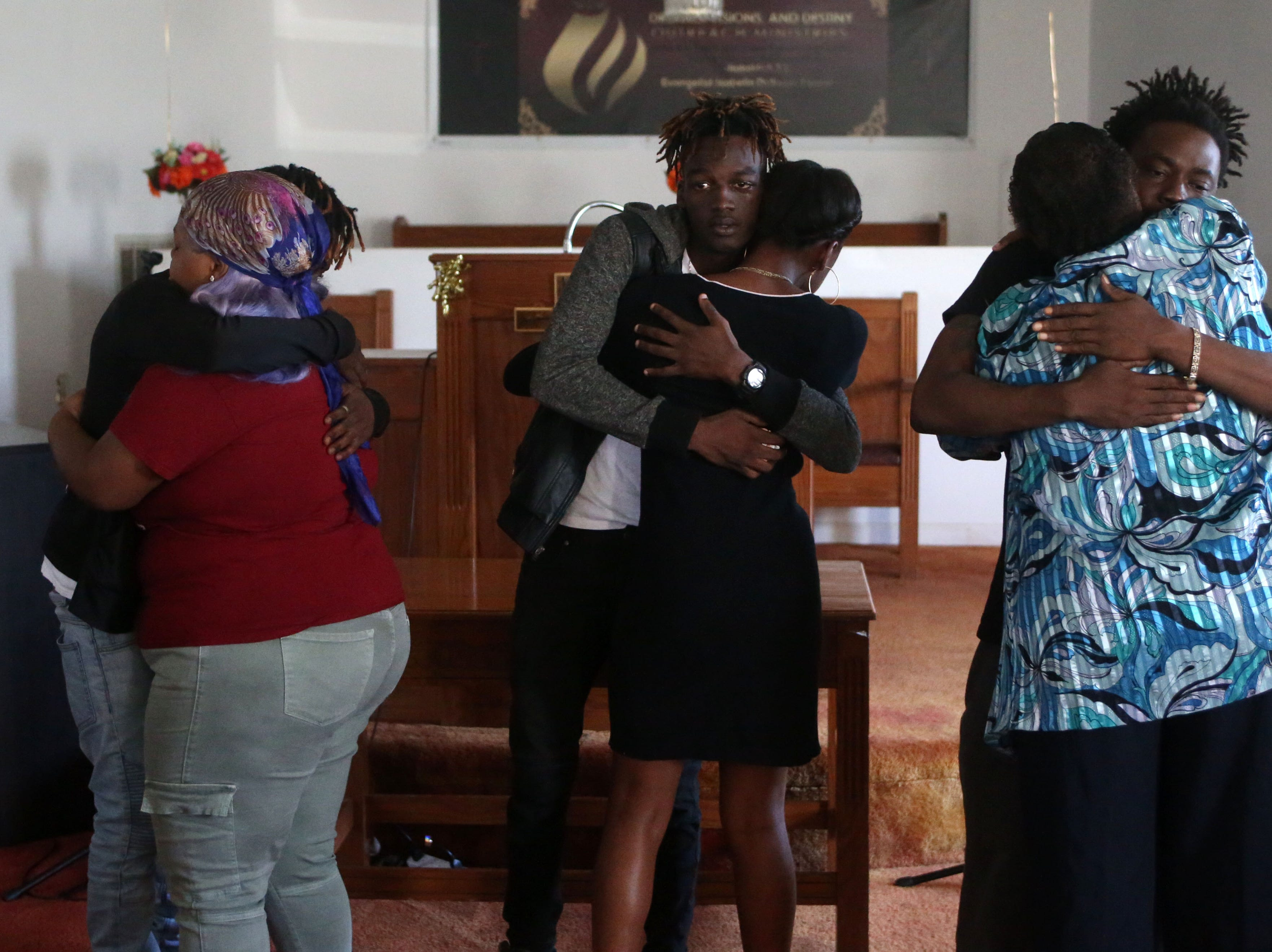 Family of Demashell Bass, a woman who could not receive medical attention and died during the hurricane, from left to right, Tyran Grant, 21, son, Tyrone Grant, 23, son, and Lawrence Williams, 33, brother, receive condolences from church members at the Dream, Vision, and Destiny (DVD) Ministry in Gretna, Fla., on Sunday Oct. 14, 2018. Hurricane Michael struck the panhandle on Wednesday, Oct. 10, 2018, leaving many small towns devastated and without power for days.