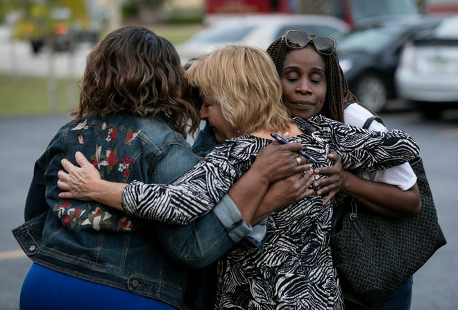 """Kristi James (center), of Fort Pierce, gives a hug to Violet Burke (left) and Beverly Douglas (right), the mother of 21-year-old Darien Douglas who was killed in the November 23rd traffic accident, while attending the fundraiser at Big Apple Pizza in Fort Pierce on Wednesday, December 19, 2018. """"I can relate to these women because my children were also in a tragic accident,"""" said James. """"We support our community."""""""