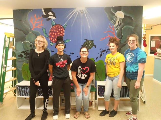 """South Fork High School art students Erika Car, left, Destiny Whitton, teacher Shelby Power,  Kalista Bomar and Erin O'Neill stand in front of the  """"under the sea"""" mural they painted on a wall at the Caring Children Clothing Children store in Stuart."""