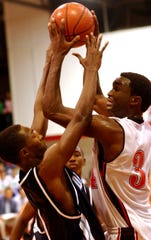 Vero Beach's Ray Cummings (right) goes for a jump shot as Erick Green, of Dr. Phillips High School in Orlando, tries to defend during the 2004 Holiday Hoopla final. Cummings was named tournament MVP that year. Thirteen other Fighting Indians players have won the award over the years.