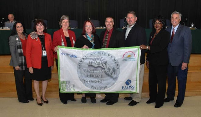 Eric Stern, representing Healthy Schools, presents the Silver Award to St. Lucie Public School for the second consecutive term. Pictured left to right: Carol Hilson, Kathryn Hensley, Debbie Hawley, Deborah Wuest, Eric Stern, Troy Ingersoll, Dr. Donna Mills, Superintendent E. Wayne Gent.