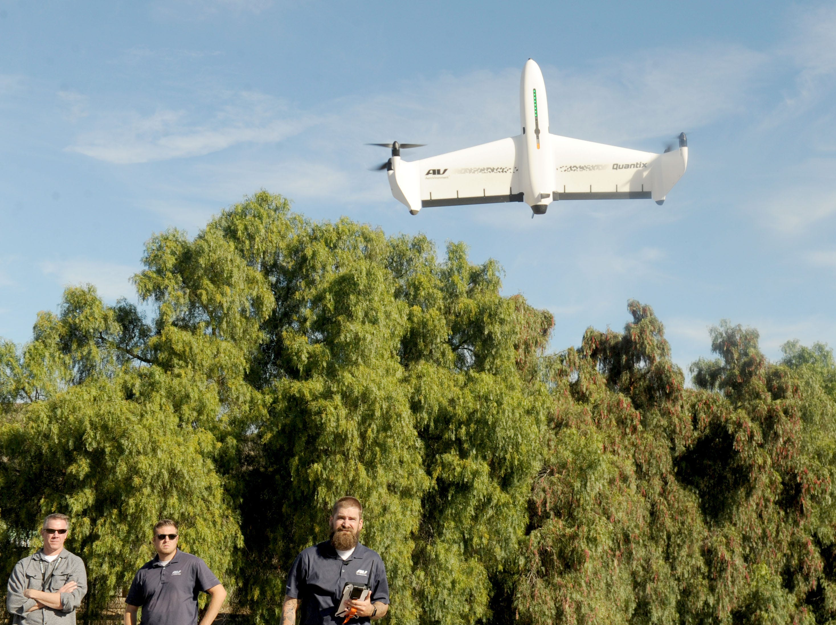 From left, Brad Carraway, Cory Schaefer and Eric Thompson AeroVironment's Quantix drone land on a open field in Moorpark.