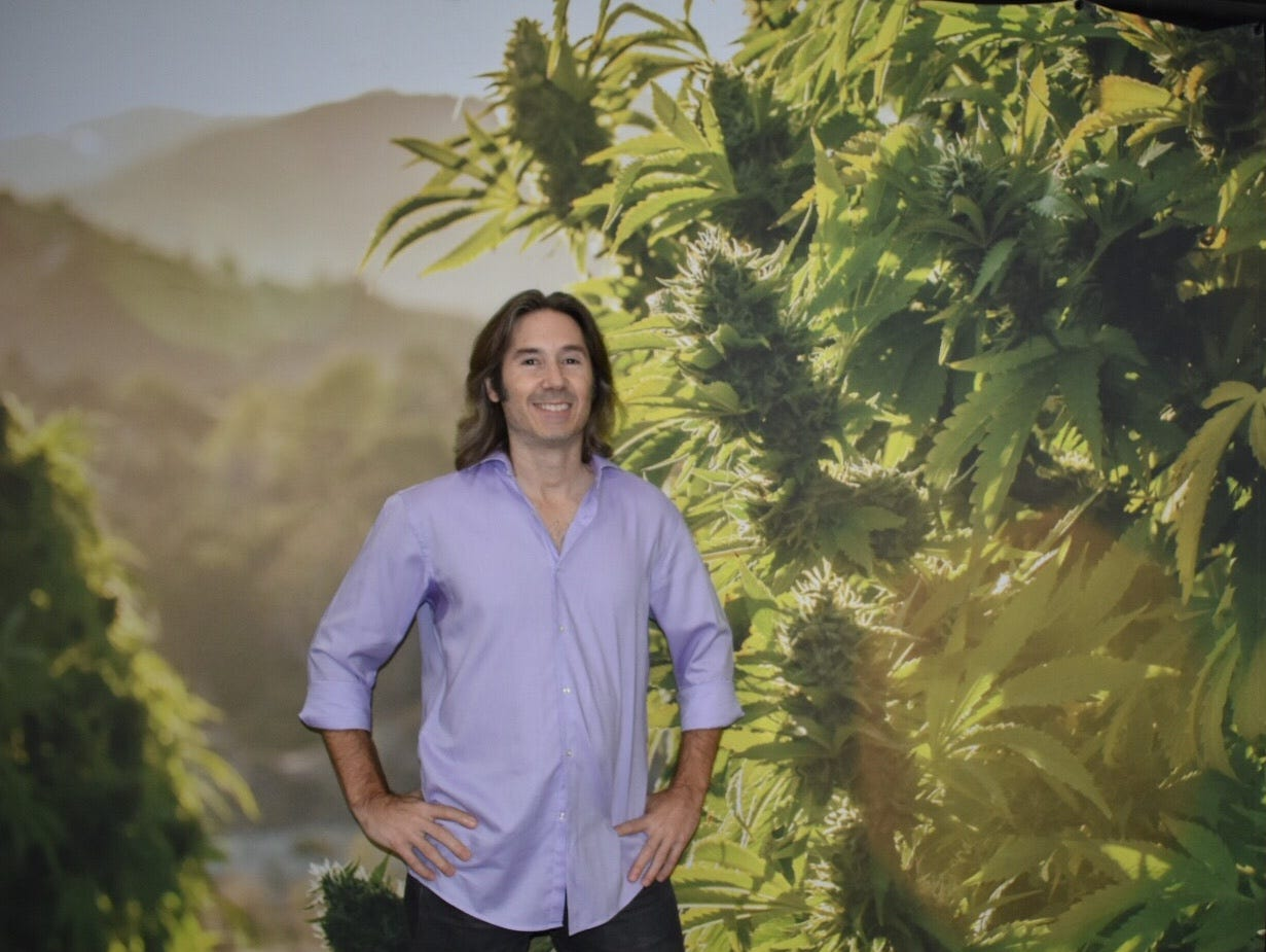 """Derek Gilman poses in front of a photograph of one of his home-grown marijuana plants, cultivated for his medical needs. Gilman hosts an online show called """"High Rollers,"""" filmed at the Green Flower cannabis education company in Ventura."""