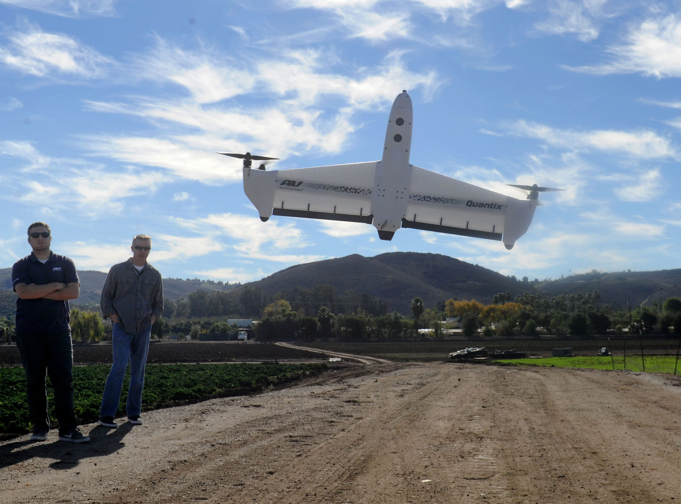 Cory Schaefer, left, and Brad Carraway watch the AeroVironment Quantix drone fly in an open field in Moorpark. The drone maker is moving its headquarters to Simi Valley. It already manufactures drones in Ventura County.