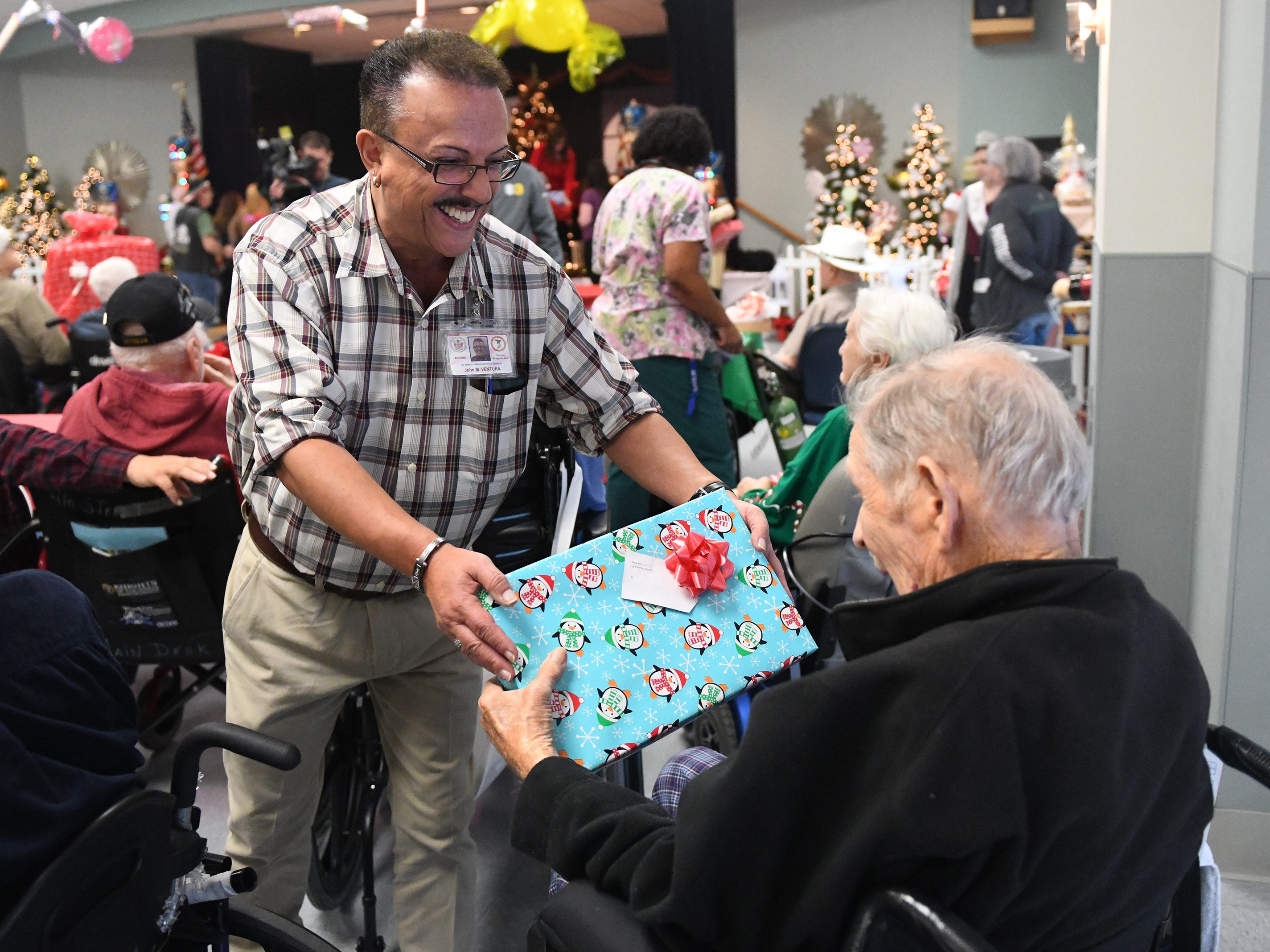 "N.J. Veterans Memorial Home staffer John Ventura helps hand out presents to residents during the eighth annual ""Second Wind Dreams"" celebration on Wednesday, December 19, 2018."