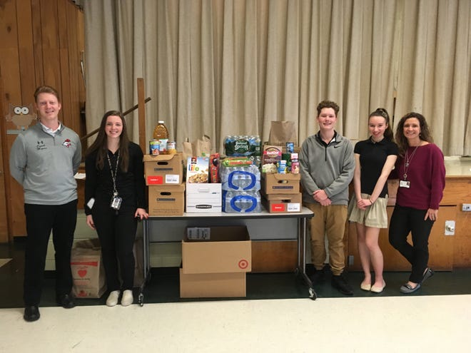 (From left) Paul Myers, school counselor for Vineland Public Schools' Applied Math & Science Academy; 11th graders Kaylee Carlson, Kevin London and Jessica Melo; and Kristina Craig, assistant principal, are pictured with items from the school's food drive which will be donated to the Vineland Soup Kitchen.