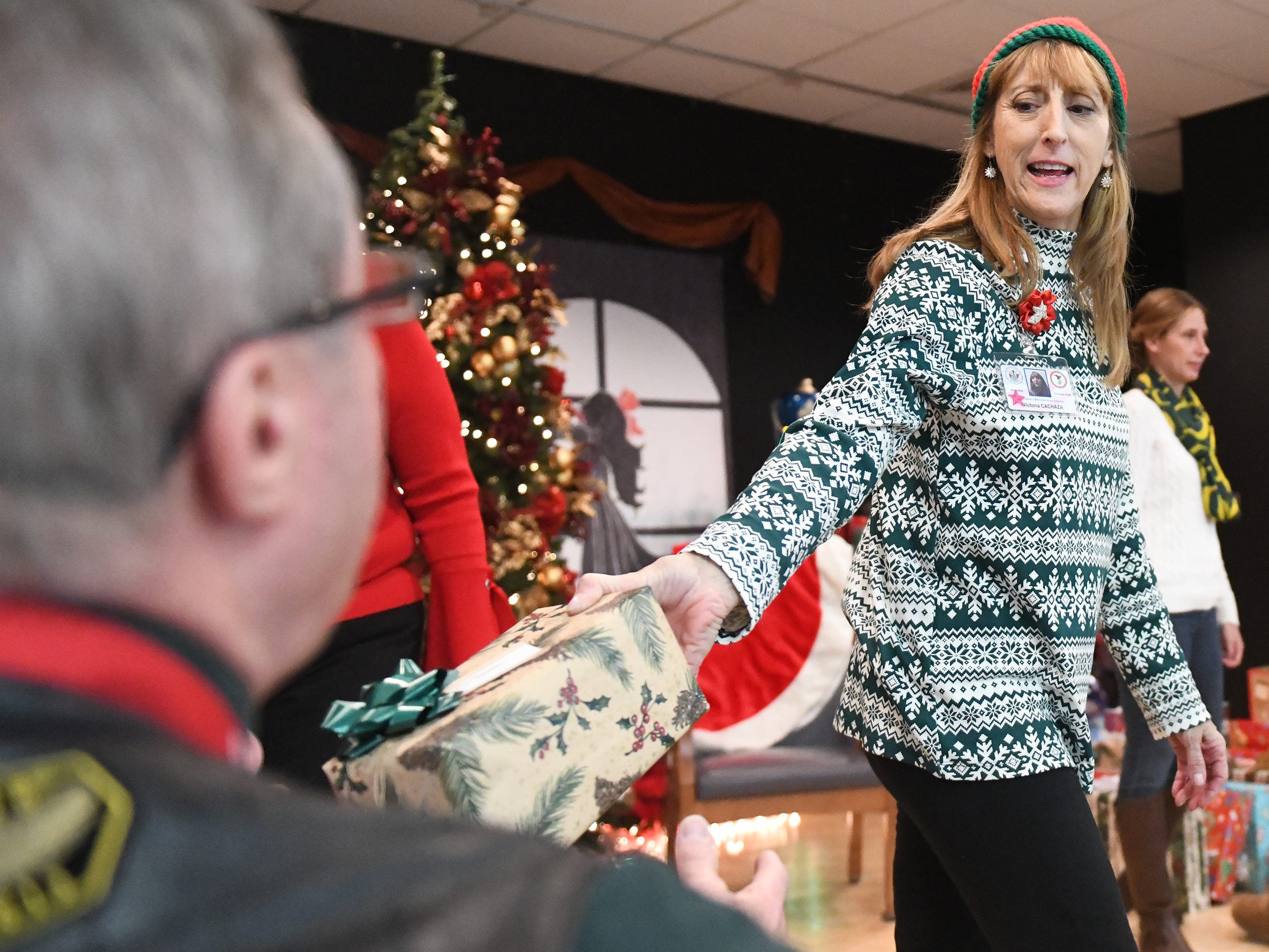 "N.J. Veterans Memorial Home staffer Victoria Cachaza helps hand out presents during the eighth annual ""Second Wind Dreams"" celebration on Wednesday, December 19, 2018."