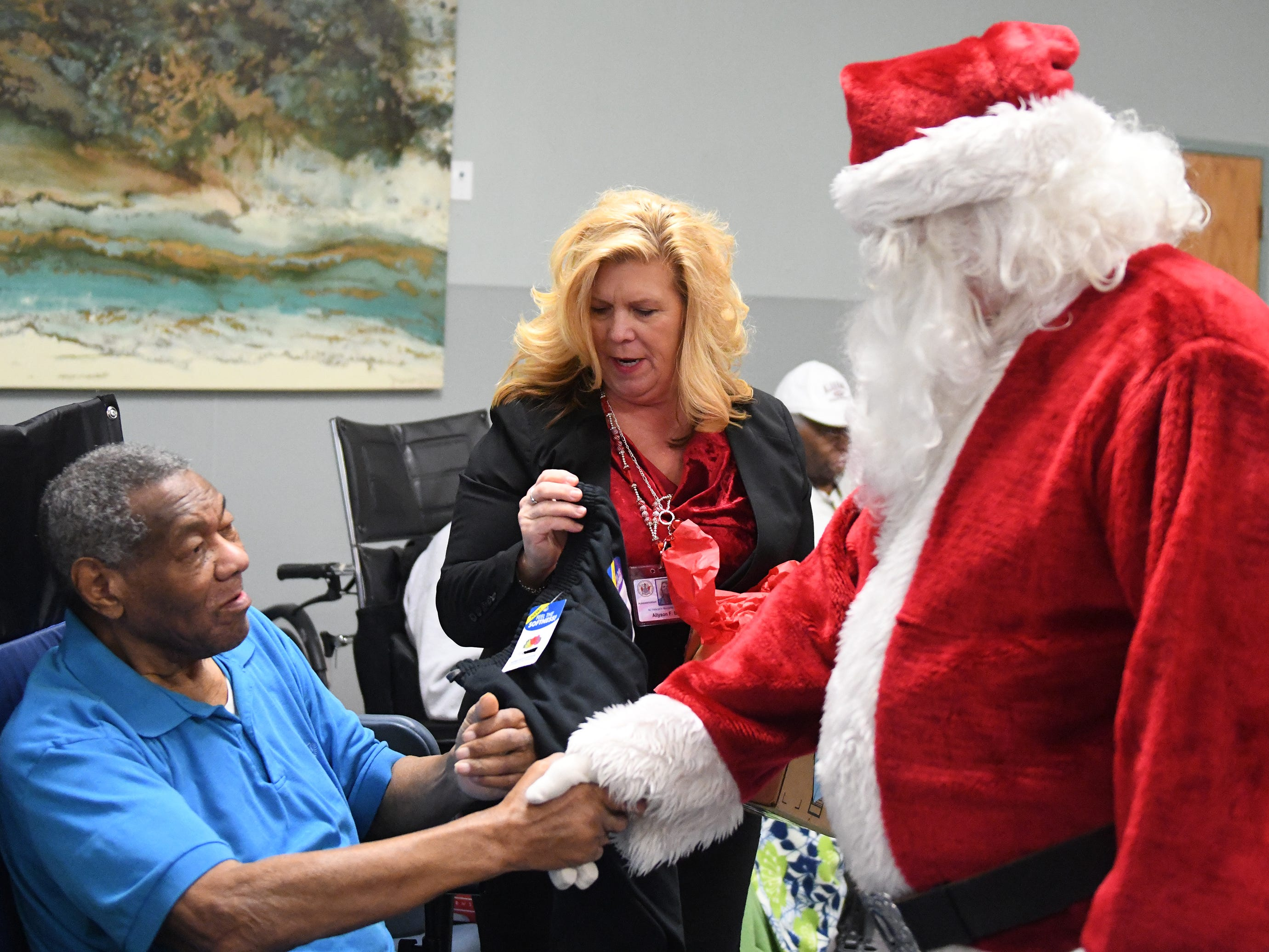 "N.J. Veterans Memorial Home CEO Allyson Bailey helps Santa deliver presents during the eighth annual ""Second Wind Dreams"" celebration on Wednesday, December 19, 2018."