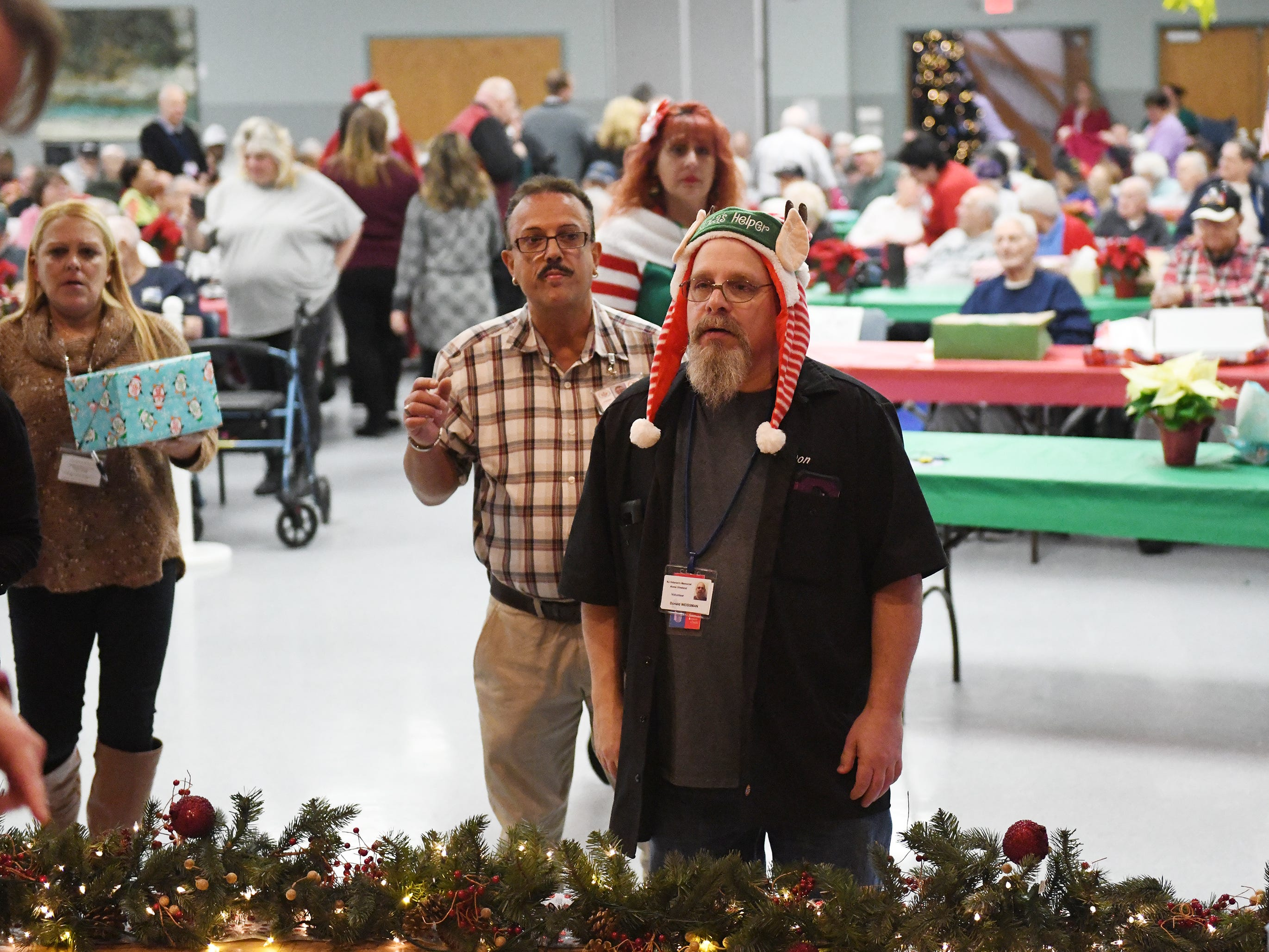 "N.J. Veterans Memorial Home volunteer Donald Weissman helps hand out presents during the eighth annual ""Second Wind Dreams"" celebration on Wednesday, December 19, 2018."