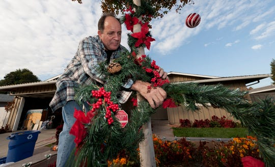 Joseph Coppola puts up Christmas lights on his house in Visalia.
