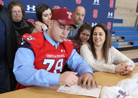 Football player Chris Fowx signs with Temple University during the signing day ceremony at Stepinac High School Dec. 19, 2018.