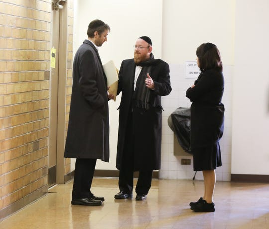 Daniel Berch, left, parent of a student at the Skill Building Center, Chaim Itzkowitz , center, and Sarah Graus, administrators with yeshiva Ateres Bnos talk during a break at  the county Department of Health meeting in Pomona on Wednesday, December 19, 2018.