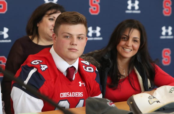 Football player Jonathan Mucciolo signs with Sacred Heart University during the signing day ceremony at Stepinac High School Dec. 19, 2018.